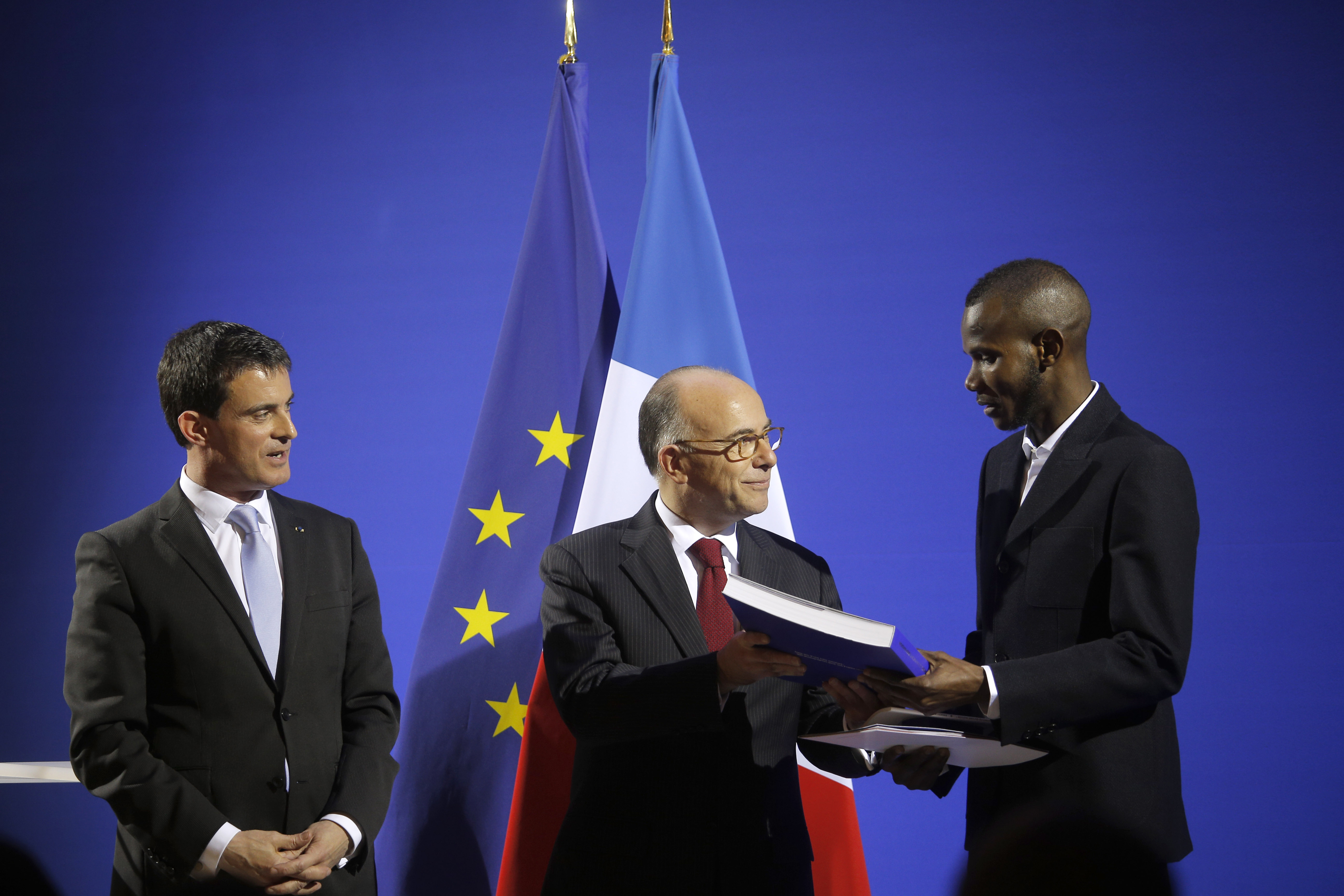 French Prime Minister Manuel Valls (L) and French Interior Minister Bernard Cazeneuve (C) award citizenship to Lassana Bathily in Paris, France, on Jan. 20, 2015.