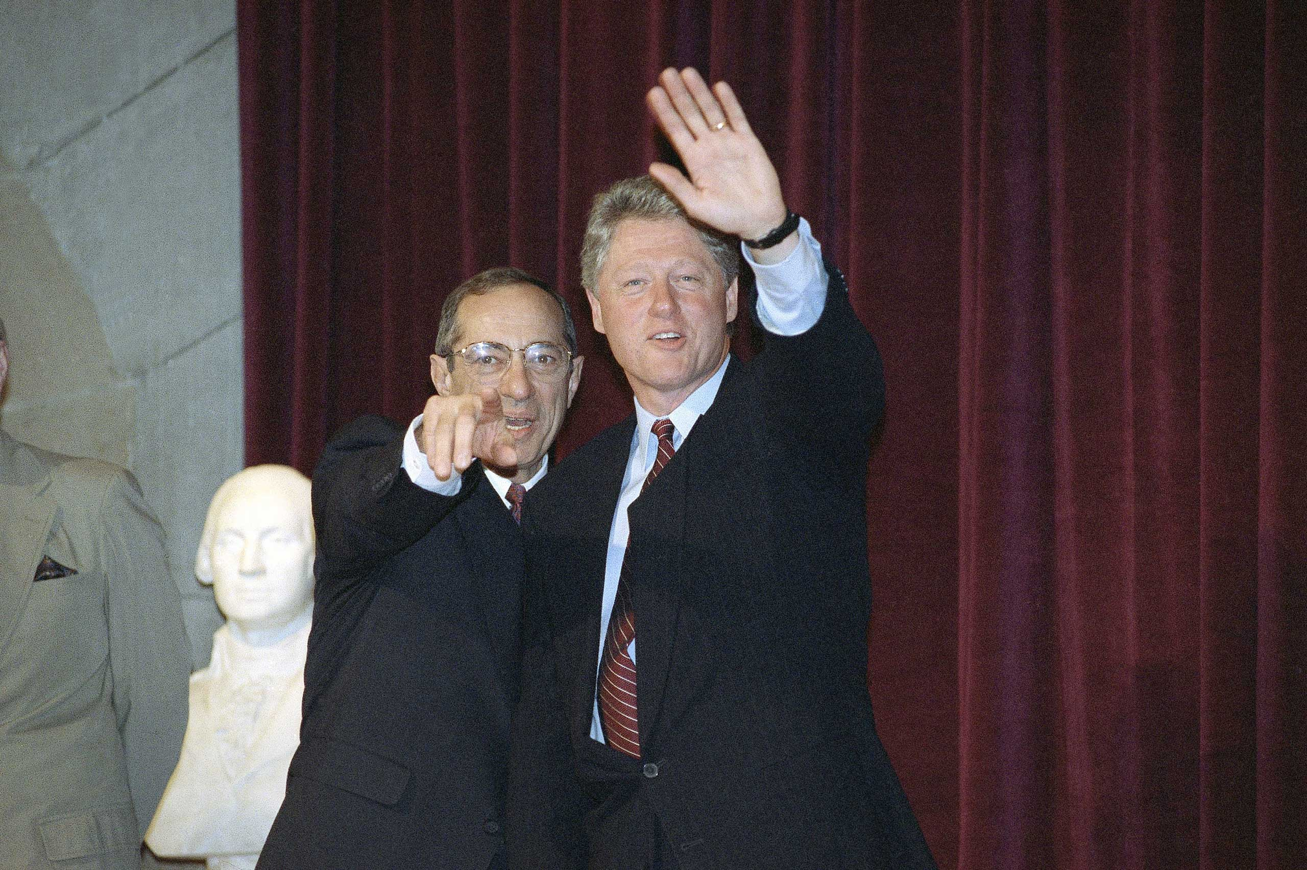 New York Governor Mario Cuomo points toward the camera as President Bill Clinton waves at the Cooper Union College in New York City on May 12, 1993.