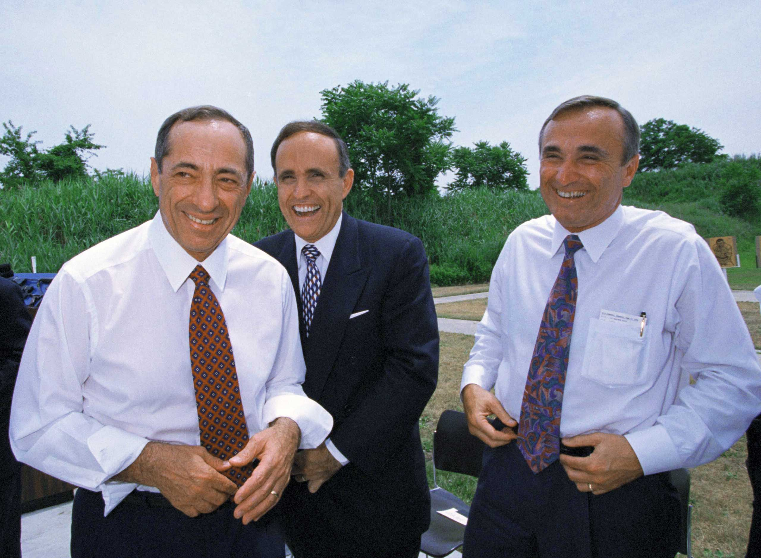 New York Governor Mario Cuomo, left, New York City Mayor Rudolph Giuliani, center, and New York City Police Commissioner William Bratton laugh during a light moment while touring the NYPD's shooting range in New York City on June 23, 1994.