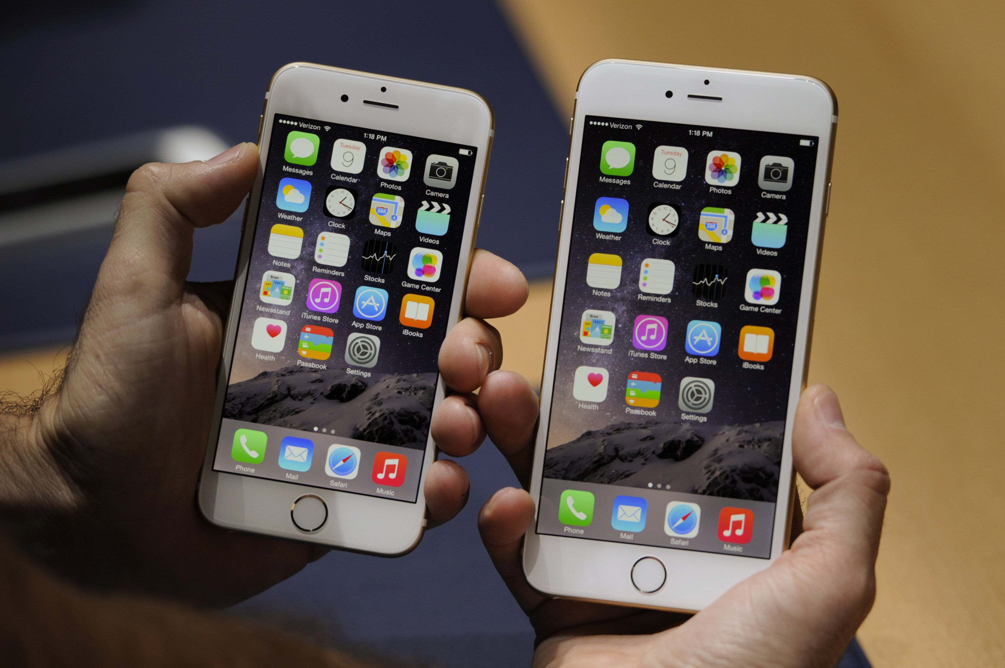 An attendee displays the new Apple Inc. iPhone 6, left, and iPhone 6 Plus for a photograph after a product announcement at Flint Center in Cupertino, Calif., on Sept. 9, 2014.