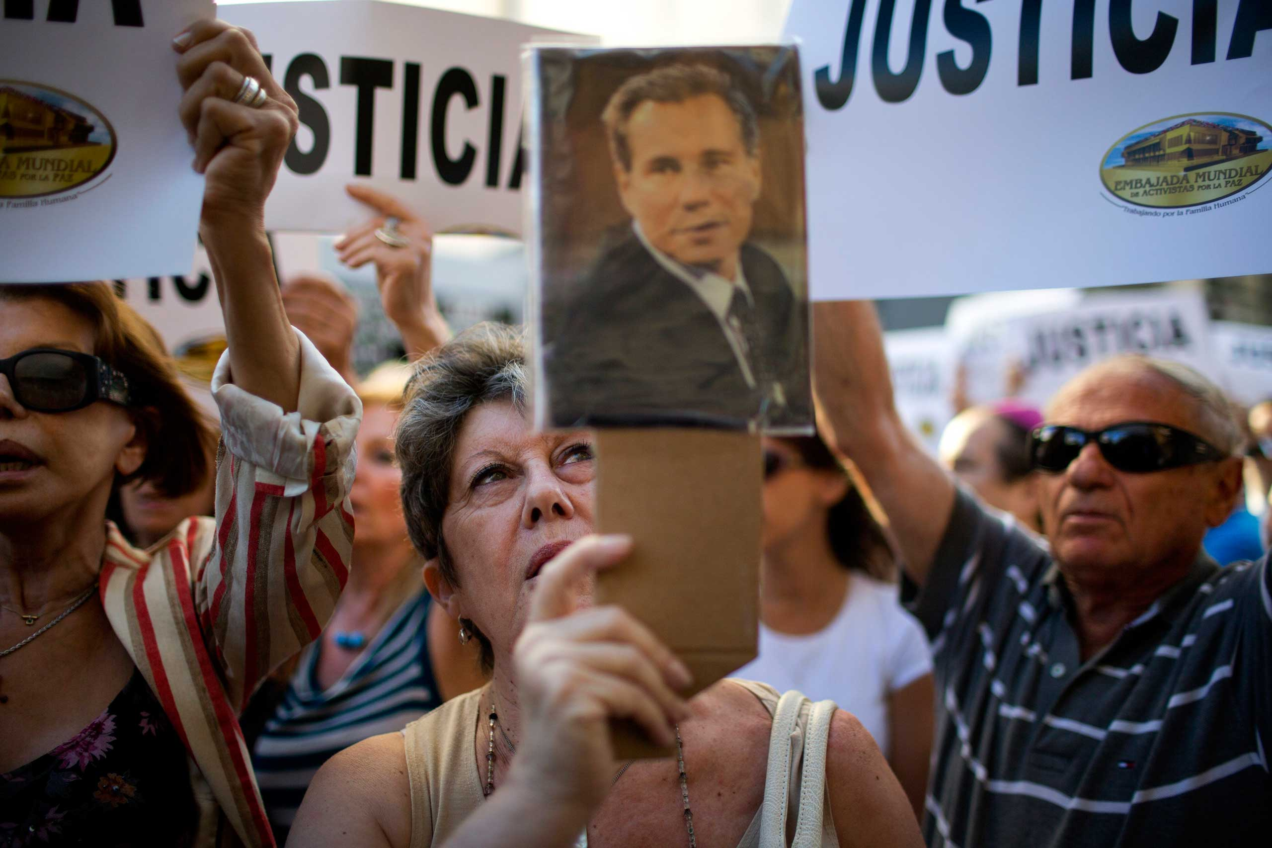 A woman chants the Argentine national anthem holding a portrait of the late prosecutor Alberto Nisman outside the AMIA Jewish community center in Buenos Aires, Jan. 21, 2015.