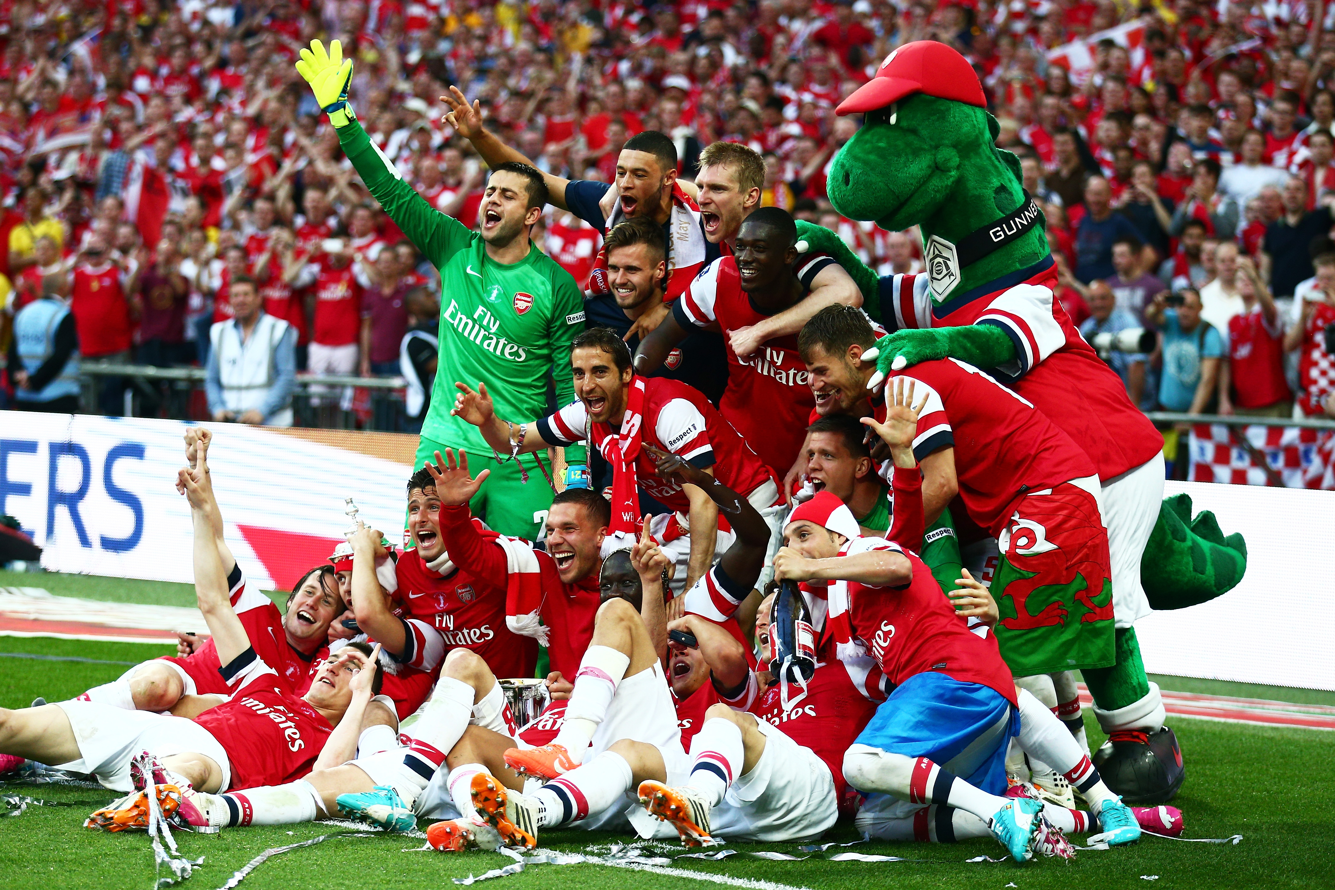 Arsenal players celebrate victory with mascot Gunnersauraus Rex after the FA Cup with Budweiser Final match between Arsenal and Hull City at Wembley Stadium on May 17, 2014 in London.