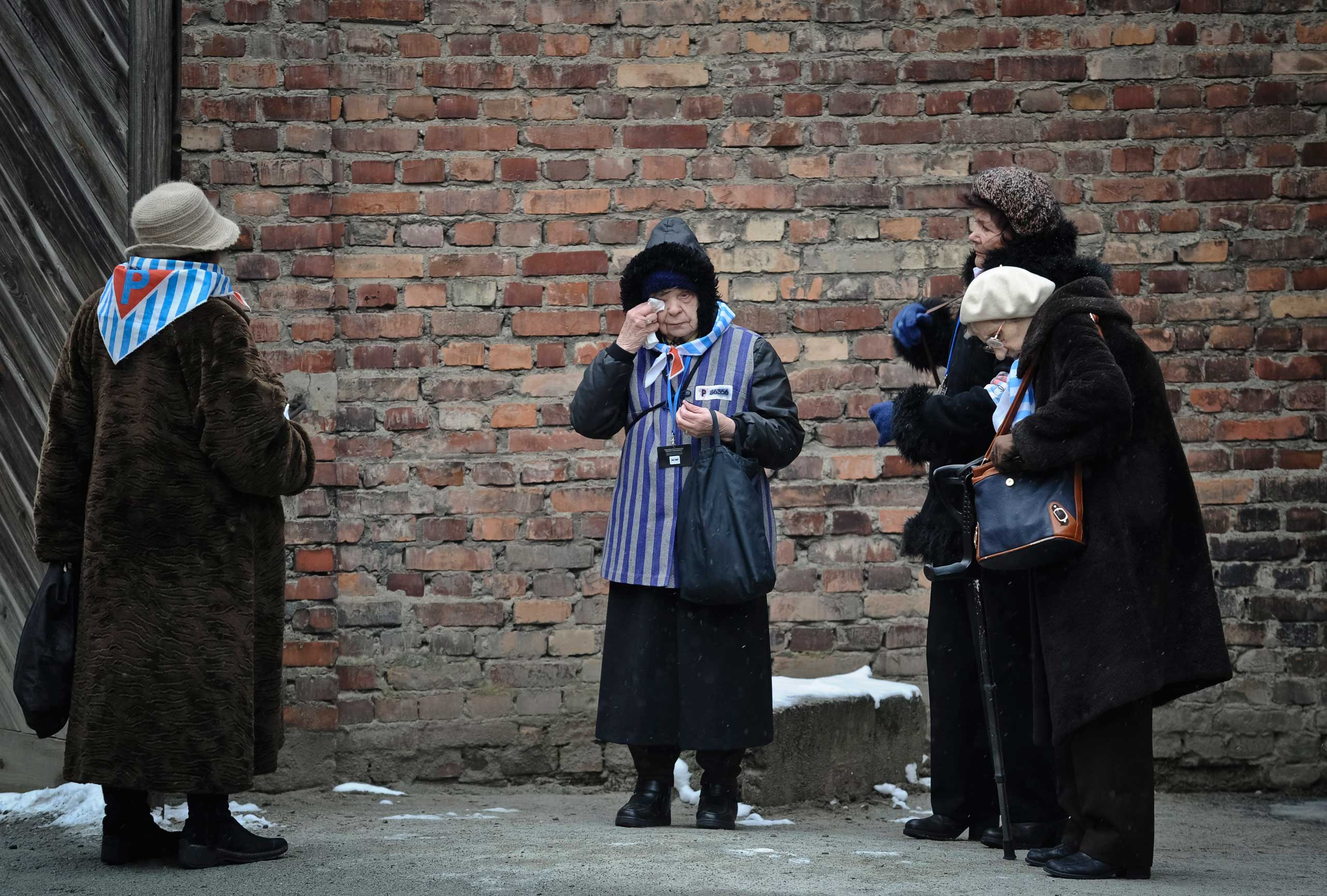 A Holocaust survivor wipes her eye while standing along with others outside a detention block of the Auschwitz Nazi death camp in Oswiecim,  Jan. 27, 2015.