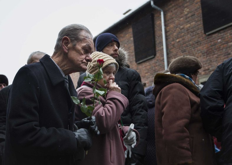 "Holocaust survivors pay tribute to fallen comrades at the ""death wall"" execution spot in the former Auschwitz concentration camp in Oswiecim, on the 70th anniversary of the liberation of the Nazi death camp on Jan. 27, 2015."
