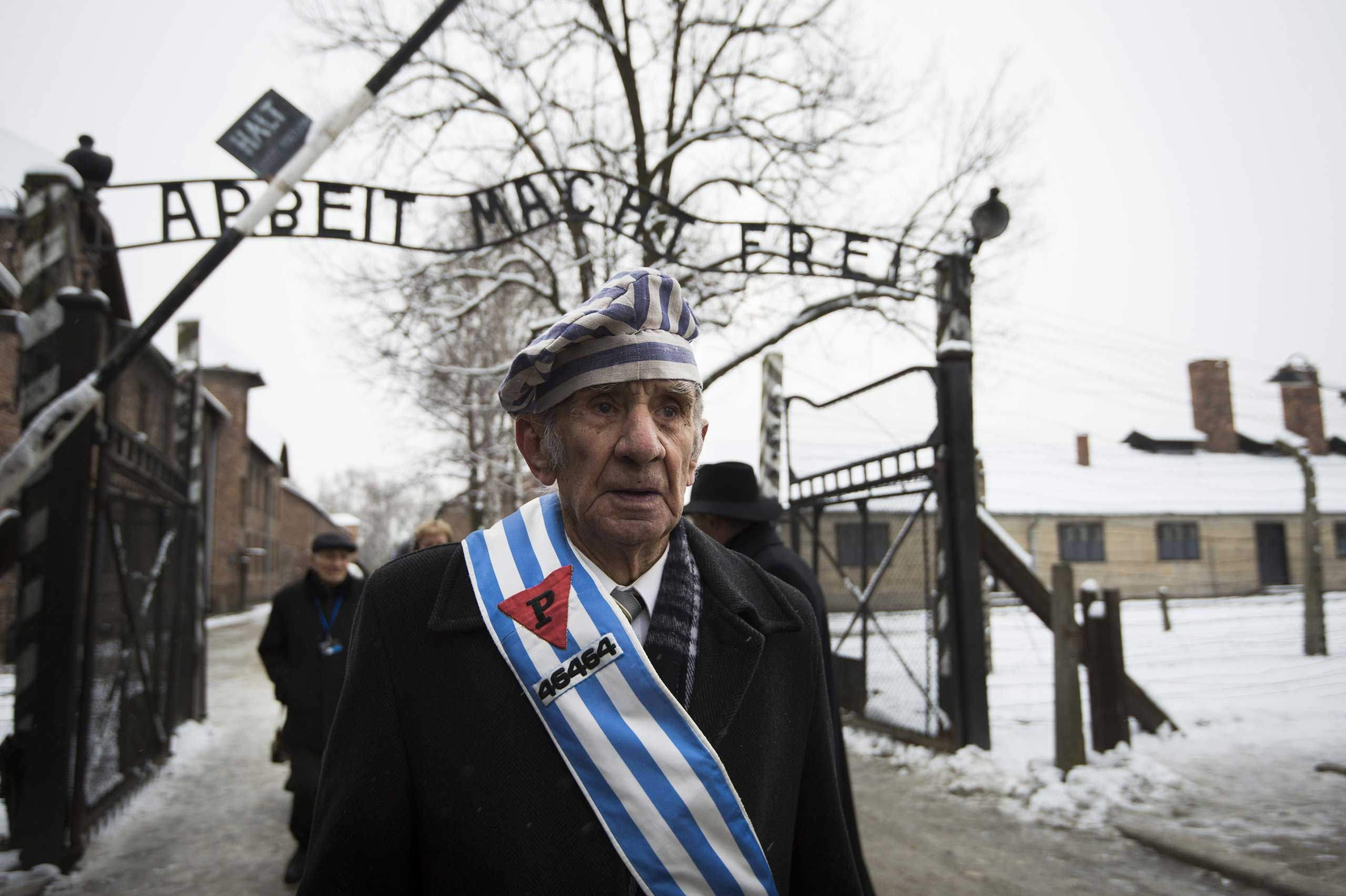 Auschwitz survivor Miroslaw Celka walks out the gate with the sign saying  Work makes you free  after paying tribute to fallen comrades at the  death wall  execution spot in the former Auschwitz concentration camp in Oswiecim, Poland, on the 70th anniversary of the liberation of the Nazi death camp on Jan. 27, 2015.
