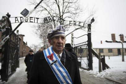 "Auschwitz survivor Miroslaw Celka walks out the gate with the sign saying ""Work makes you free"" after paying tribute to fallen comrades at the ""death wall"" execution spot in the former Auschwitz concentration camp in Oswiecim, Poland, on the 70th anniversary of the liberation of the Nazi death camp on Jan. 27, 2015."