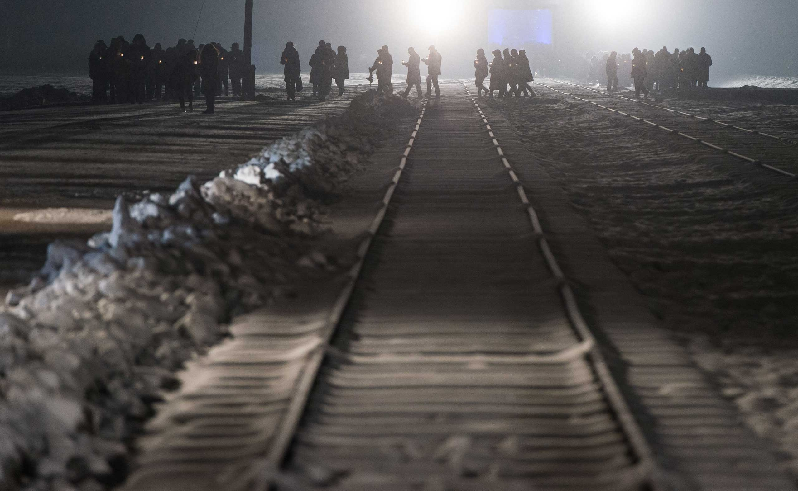 Auschwitz survivors and families visit the Birkenau Memorial carrying candles on Jan. 27, 2015 in Oswiecim, Poland.