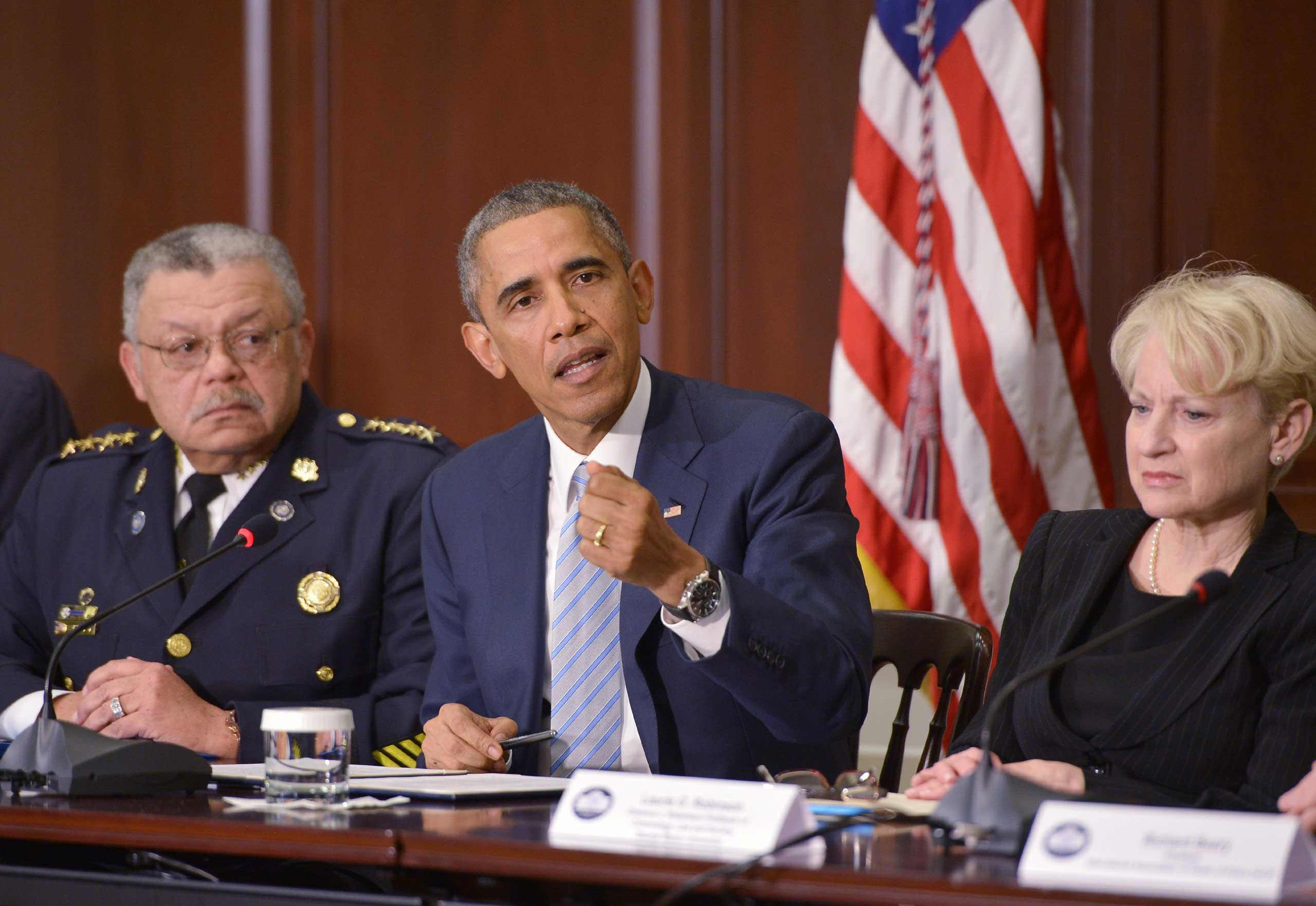 US President Barack Obama speaks after a meeting on building trust in communities following Ferguson unrest, with Philadelphia Police Commissioner Charles Ramsey (L) and George Mason University professor of Criminology, Law and Society Laurie Robinson, who were appointed by Obama to chair a task force on policing, at the Eisenhower Executive Office Building in Washington on Dec. 1, 2014.