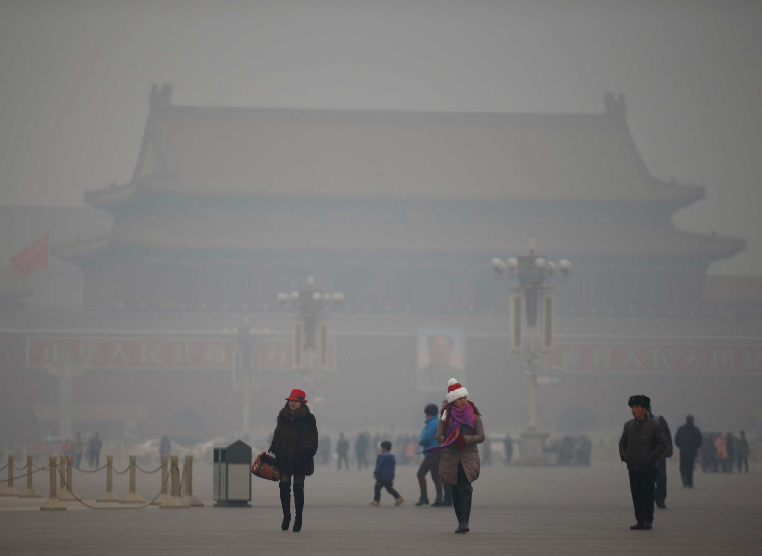 Visitors take a walk during a polluted day at Tiananmen Square in Beijing on Jan. 15, 2015.