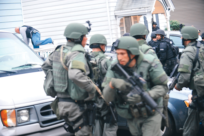 <b>6:02.14 p.m.</b>  Tactical Police Officers converge on the house where 19-year-old Boston Marathon bombing suspect Dzhokhar Tsarnaev was hiding at the time of his capture in Watertown, Mass., April 19, 2013.