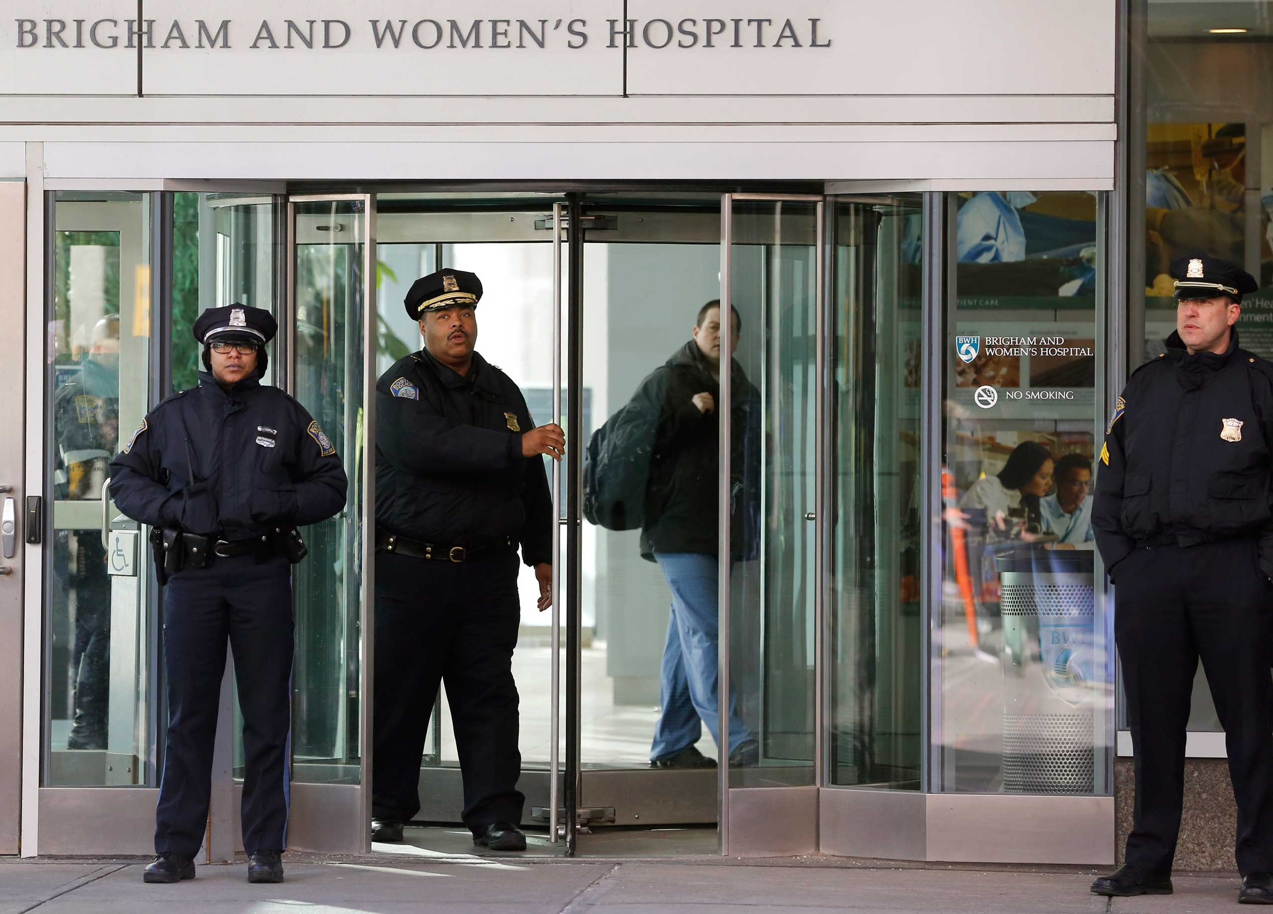 Boston Police Superintendent-in-Chief William Gross, center left, walks through a revolving door as he departs the Shapiro building at Brigham and Women's Hospital, Jan. 20, 2015 in Boston.