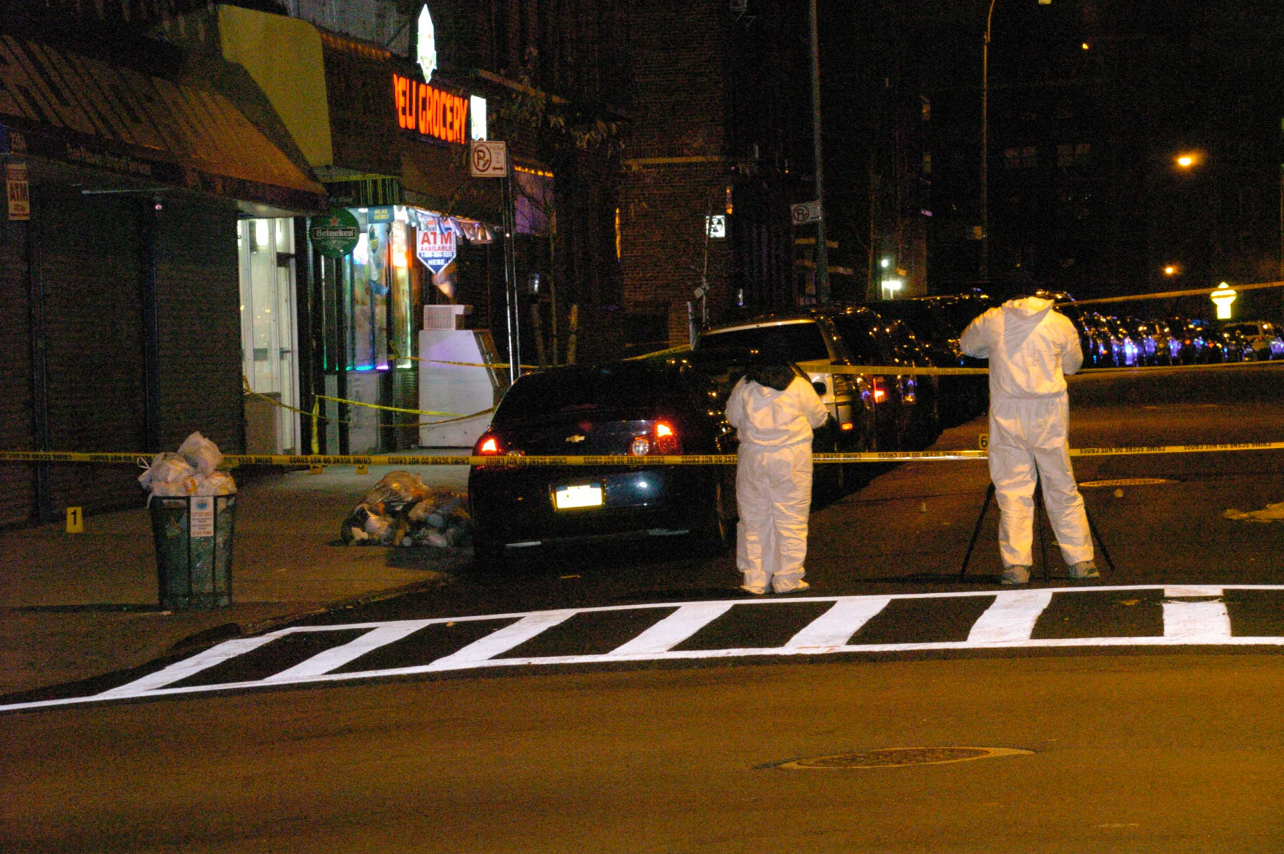 Investigators examine the crime scene where two NYPD officers were shot in the Bronx borough of New York City, early on Jan. 6, 2014.