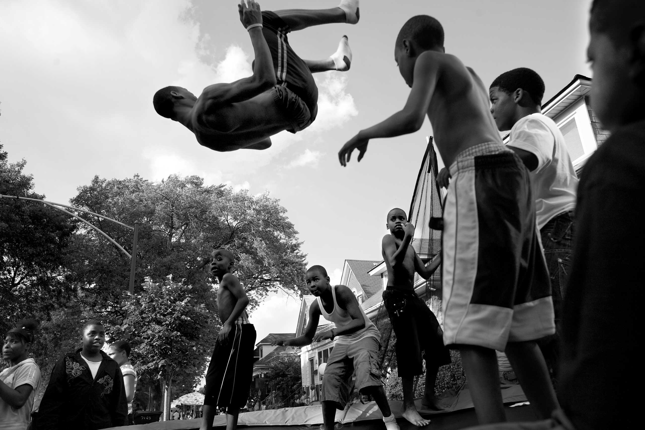 Kids jump off a trampoline during a block party. Auburn Gresham, Chicago, 2013.