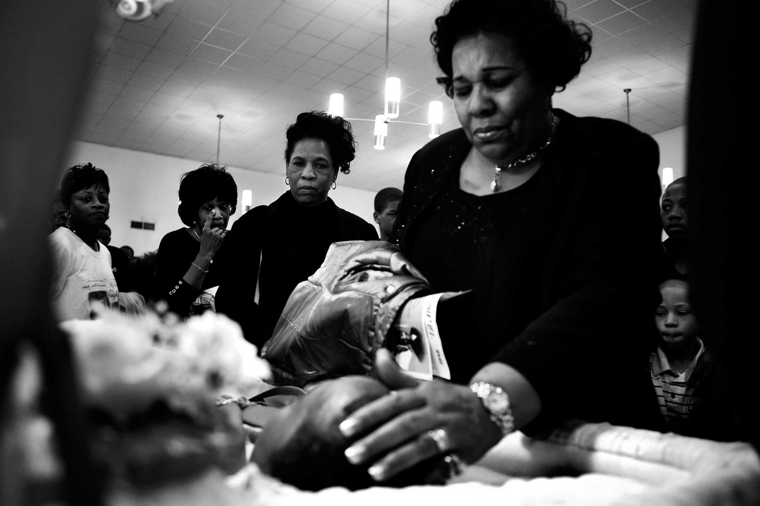 "Family members gather around Albert Vaughn's coffin to say goodbye. ""Lil Al"" was beaten to death with a baseball bat by Nathaniel Tucker. The conflict began when Vaughn, 18, confronted Tucker's cousin, who had gotten into an argument with Vaughn's younger brother. Englewood, Chicago, 2008."