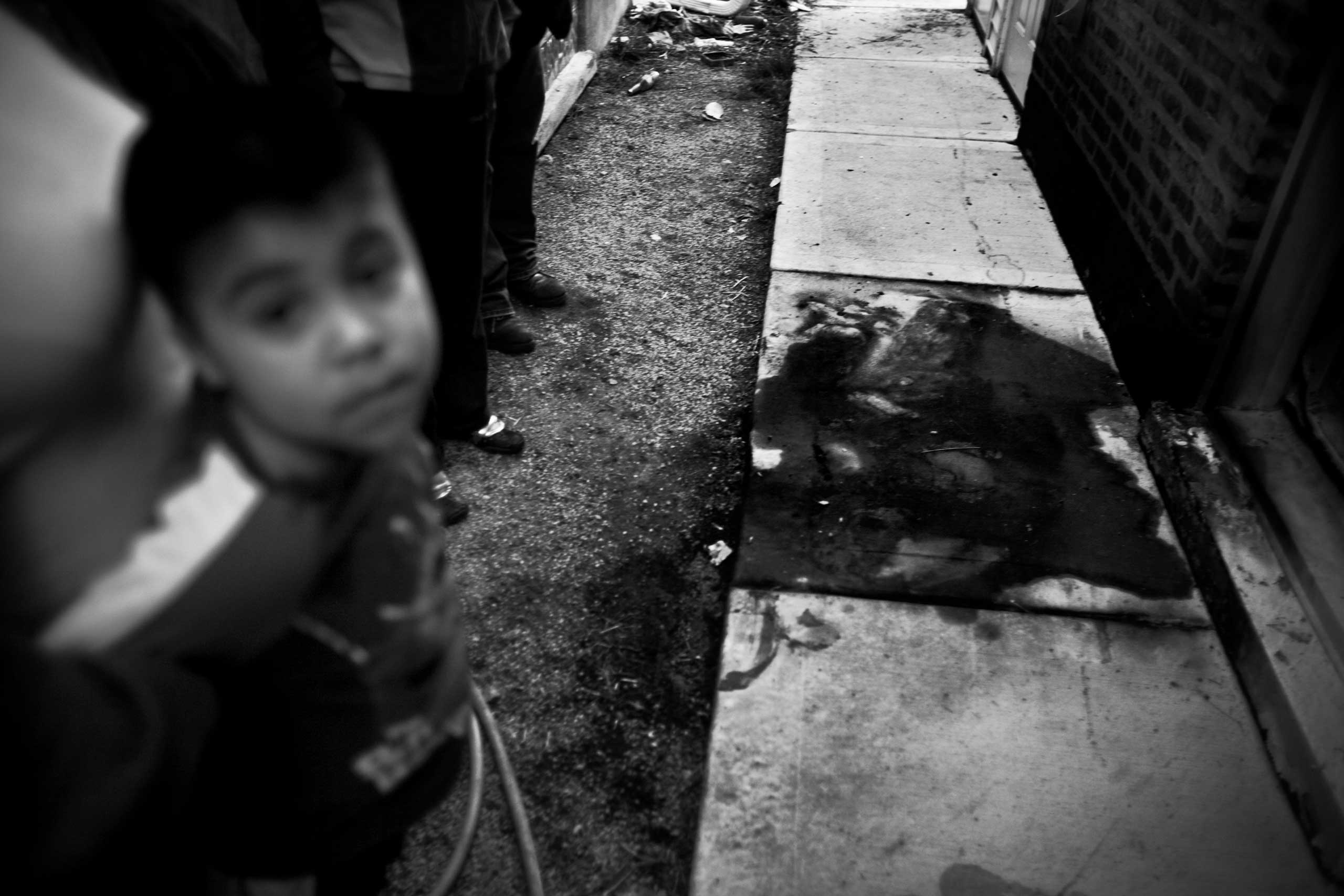 Alex Arellano, 15, was shot and burned after being hit with bats and then struck by a car that was chasing him. Gage Park, Chicago, 2009.                                                                      Side caption: Burn marks in the gangway where 15-year-old Alex Arellano was murdered.