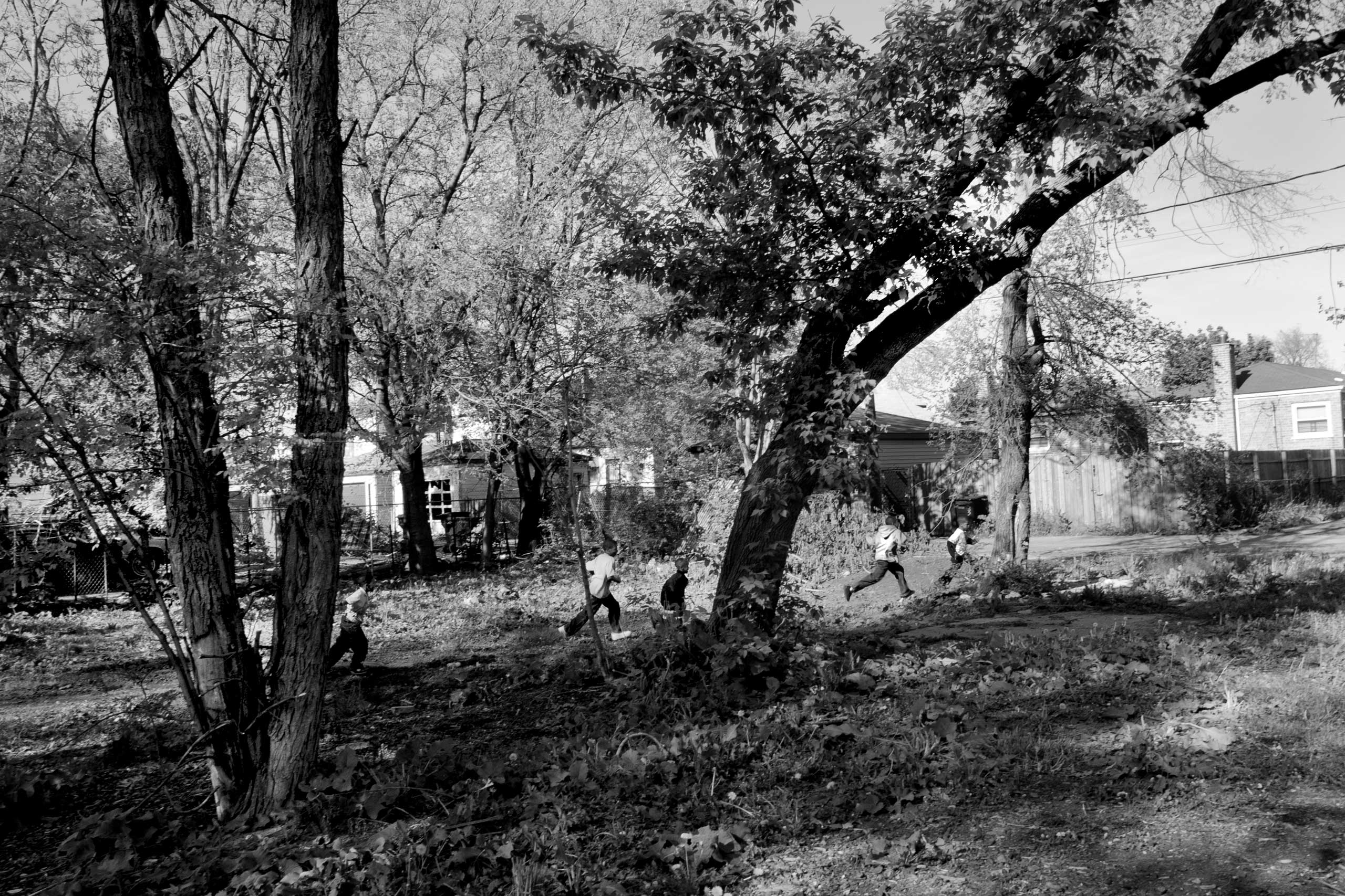 Boys play in an empty lot where homes once stood. Today, all that remains are trees and broken glass surrounded by abandoned homes. Englewood, Chicago, 2007.