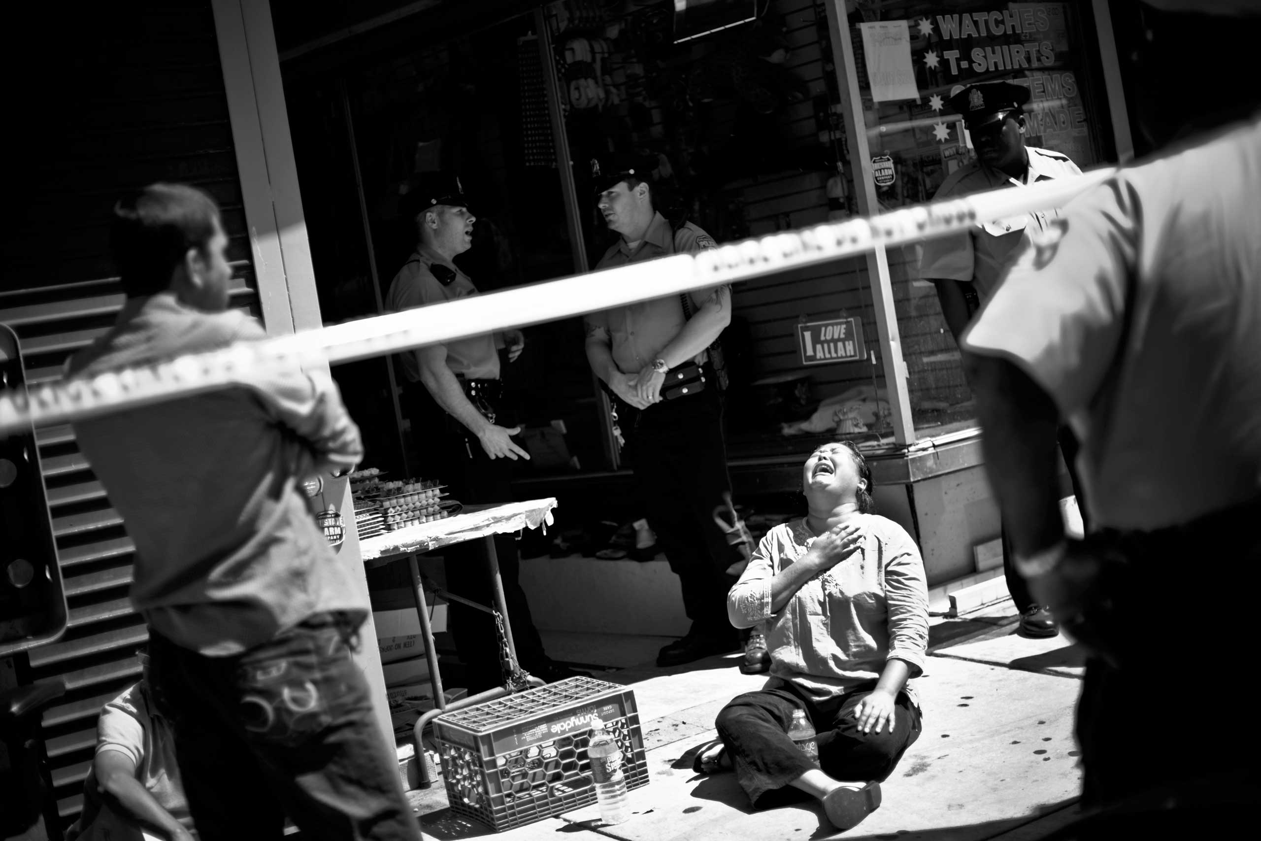 The mother of Fakhur Uddin, a 20-year old college student who was bound with duct tape and shot in the back of the head inside his family's Philadelphia store, collapses to the ground and weeps as police investigate the scene. Germantown, Philadelphia, 2008.