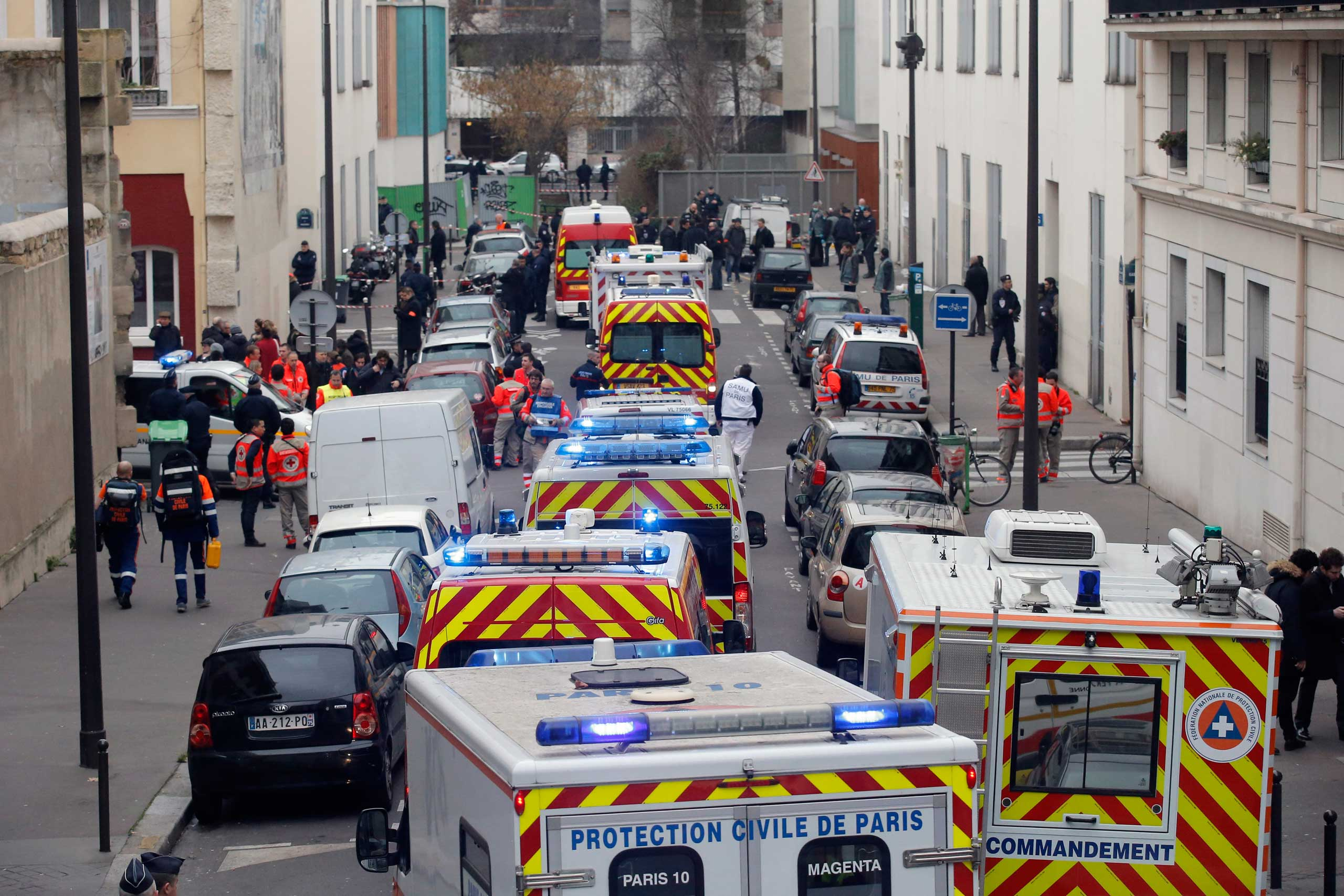 Ambulances gather in the street outside the French satirical newspaper Charlie Hebdo's office, in Paris, Jan. 7, 2015.