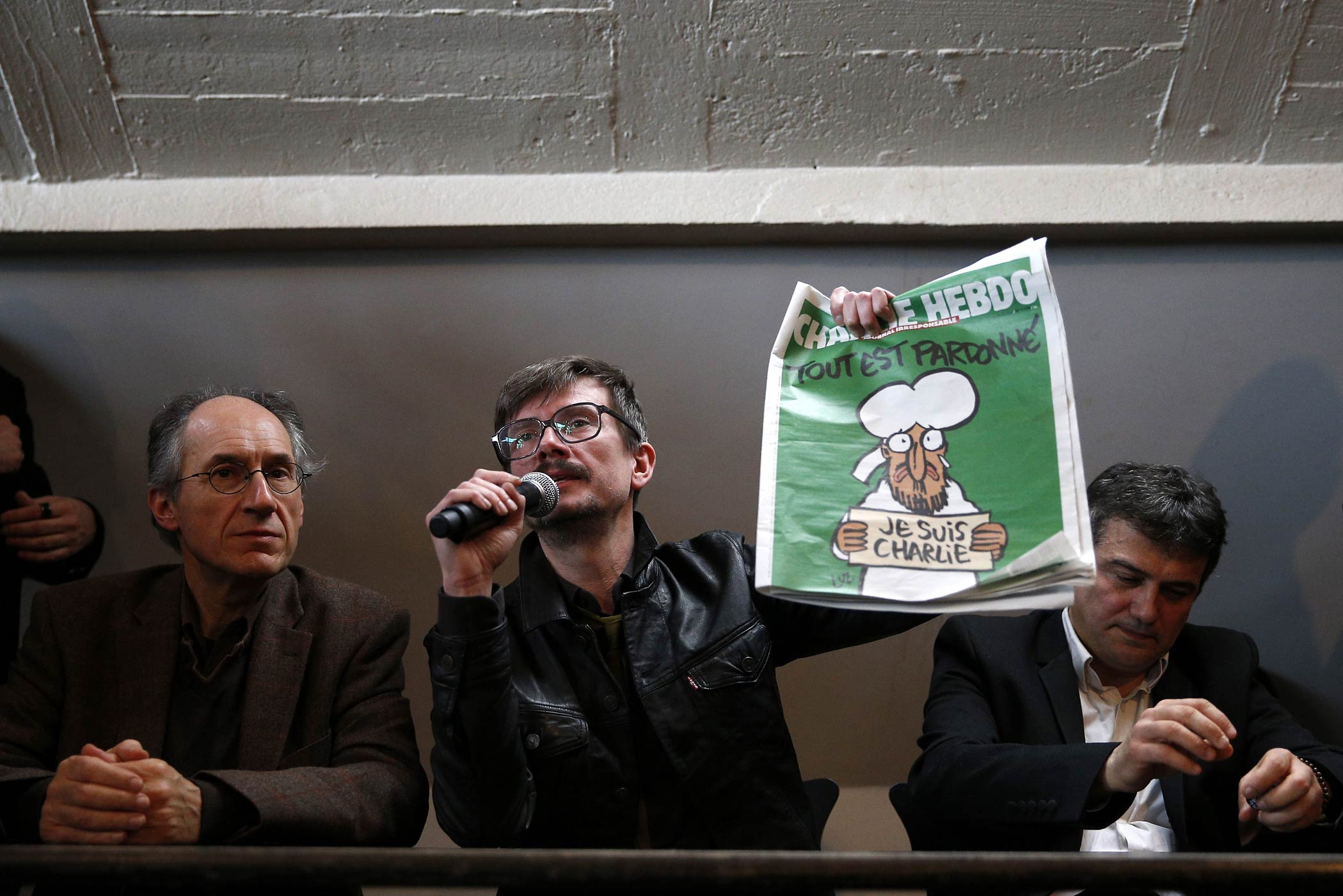 The new editor-in-chief of French satirical magazine Charlie Hebdo, Gerard Biard, caricaturist Luz, Journalist Patrick Pelloux and editor-in-chief of French newspaper Liberation, Laurent Joffrin, hold a press conference about the next Charlie Hebdo edition, at the Liberation newspaper headquarters, in Paris, Jan. 13, 2015.