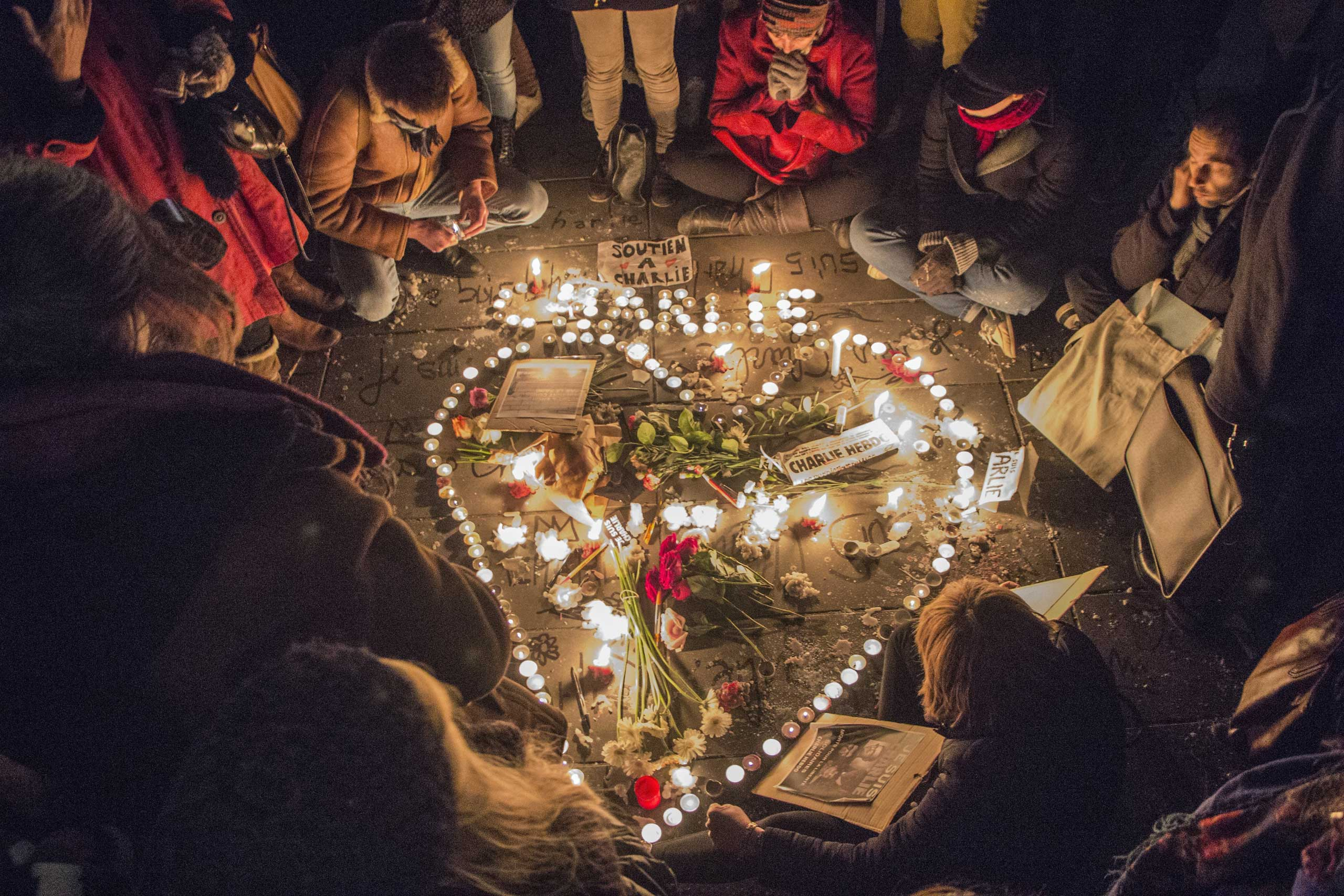 A tribute of flowers and candles in the shape of a heart is set up at Place de la Republique in Paris in memory of the victims of the Charlie Hebdo terrorist attack, on Jan. 7, 2015 in Paris.