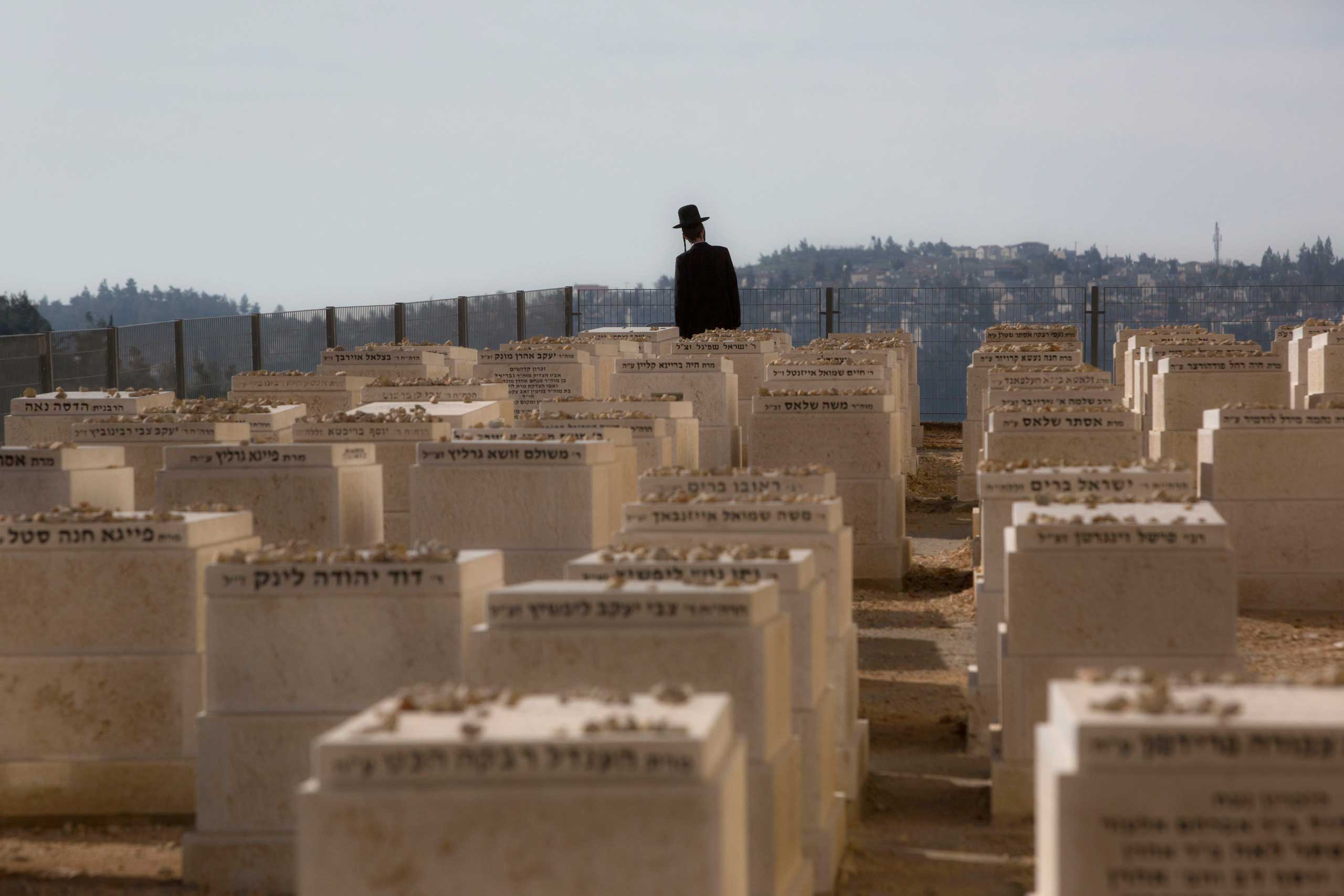 An ultra-Orthodox Jewish man walks in a cemetery during the funeral of four French Jewish victims of the attack last week on a kosher grocery store in Paris, in Jerusalem, Jan. 13, 2015.