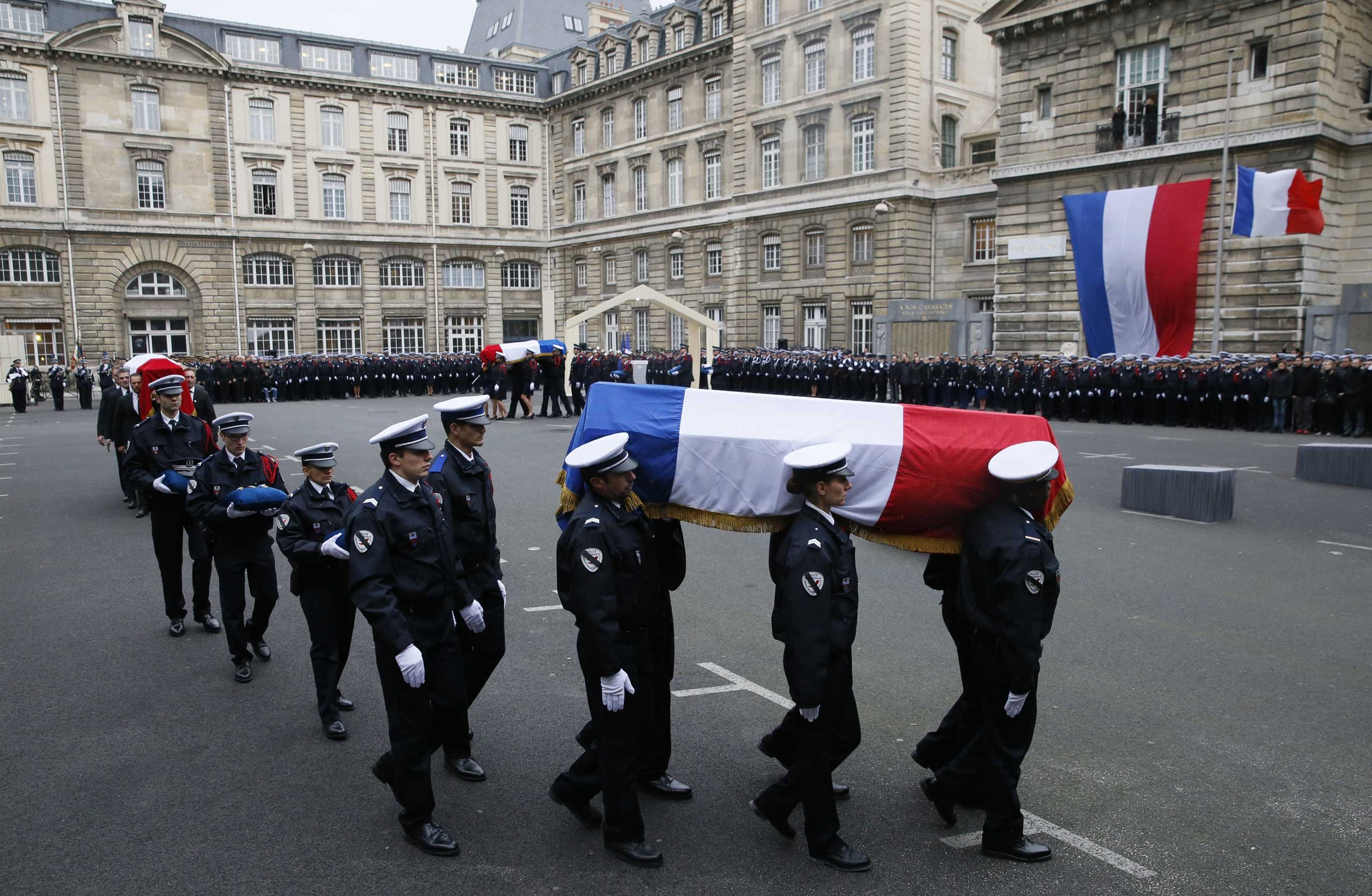 Police officers carry the flag-draped coffins of three police officers killed in the recent terror attacks during a ceremony to posthumously decorate them with the Légion d'Honneur at the Invalides in Paris, France, on Jan. 13, 2015.