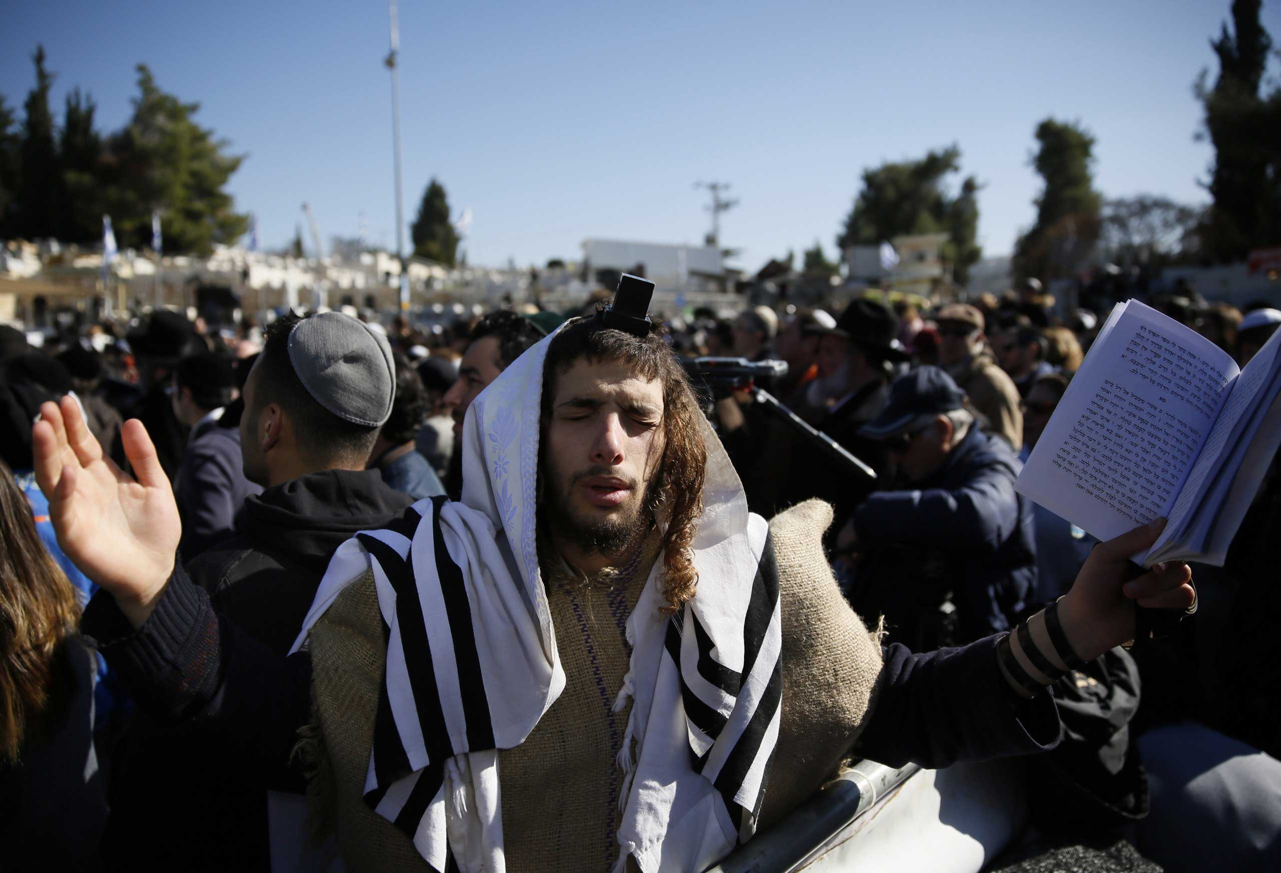 An ultra-Orthodox man prays at the funeral of four Jews, who were killed in a terrorist attack on a kosher supermarket in Paris last week, at a cemetery in Jerusalem on Jan. 13, 2015.