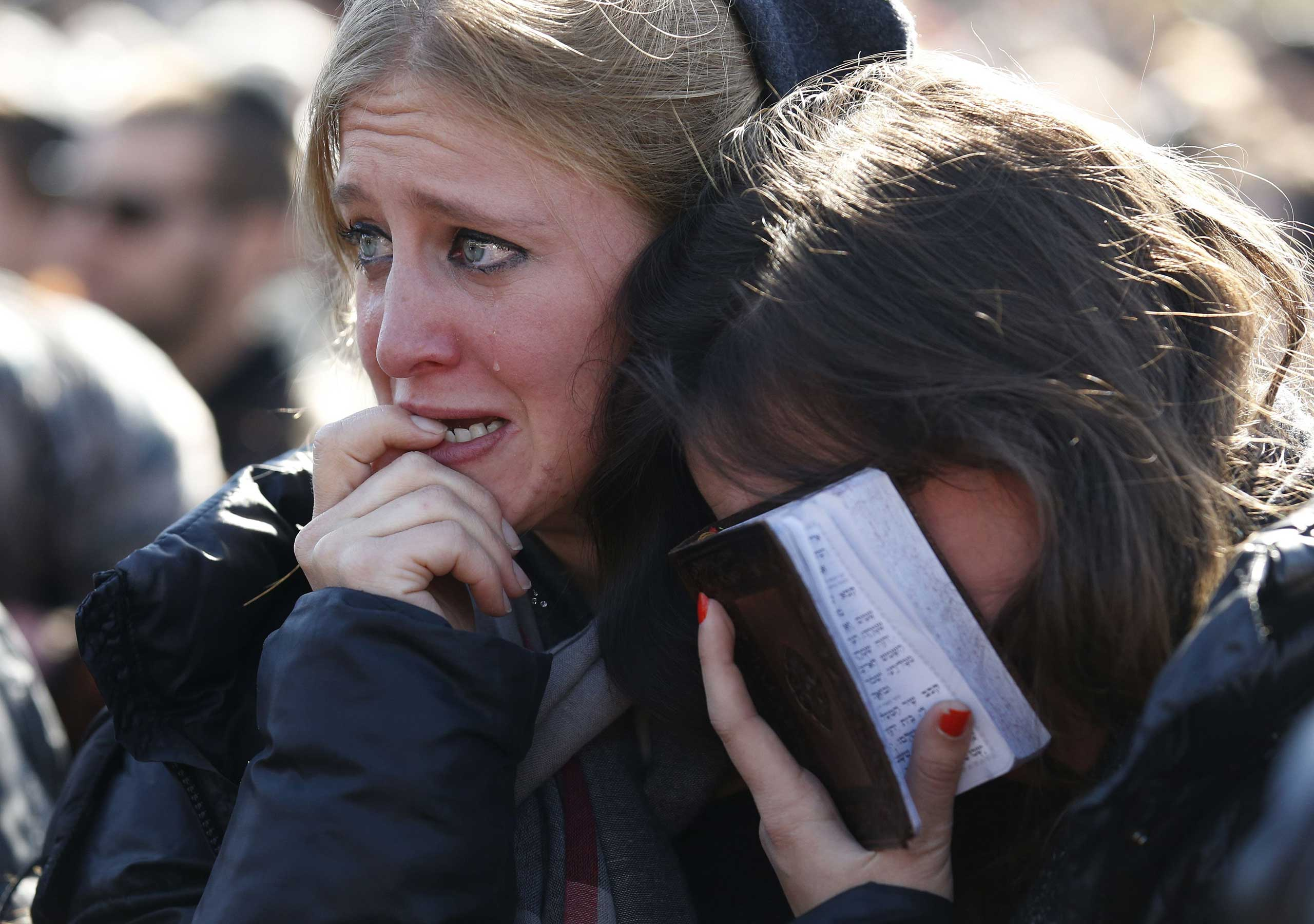 Mourners react during the funeral of four Jews, who were killed in last week's attack on a kosher supermarket in Paris, while attending the service in Jerusalem on Jan. 13, 2015.