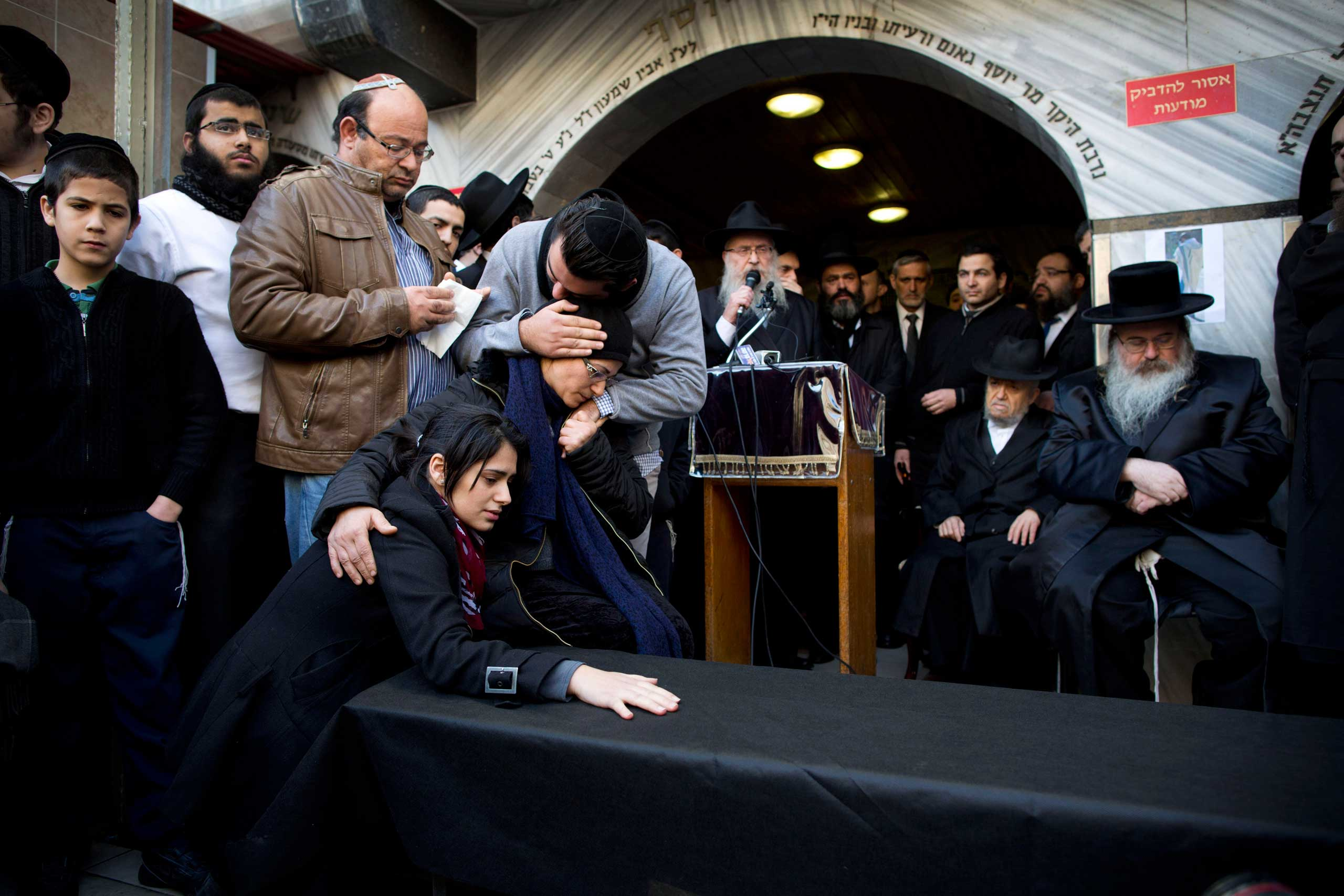 Family and relatives of Yoav Hattab, a Jewish victim of the attack on a kosher grocery store in Paris, gather around a symbolic coffin for his funeral procession in Bnei Brak, near Tel Aviv, Israel,  on Jan. 13, 2015.