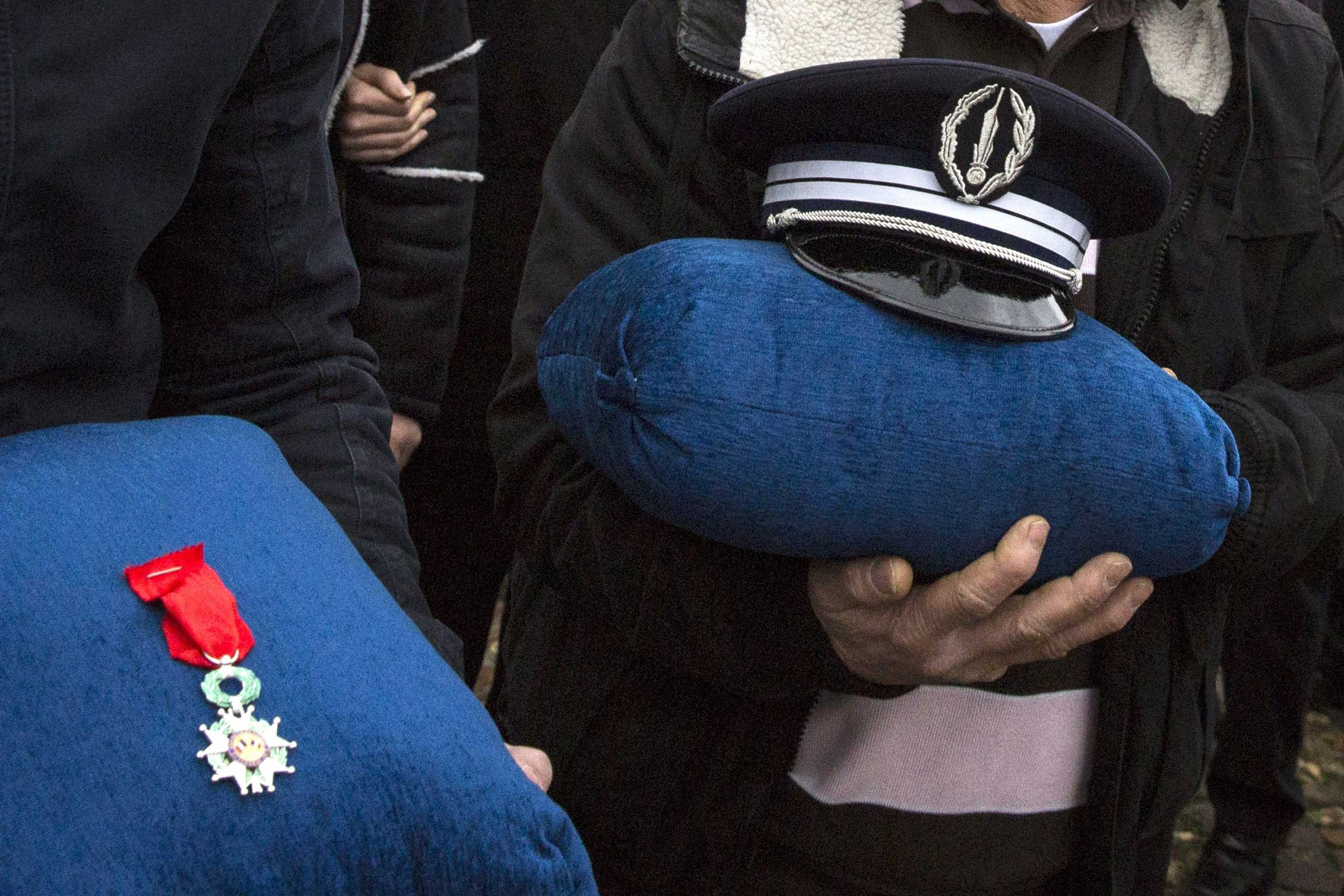 Family members of police officer Ahmed Merabet hold his cap and his Légion d'Honneur decoration during his funeral at a Muslim cemetery in Bobigny, France, on Jan. 13, 2015.