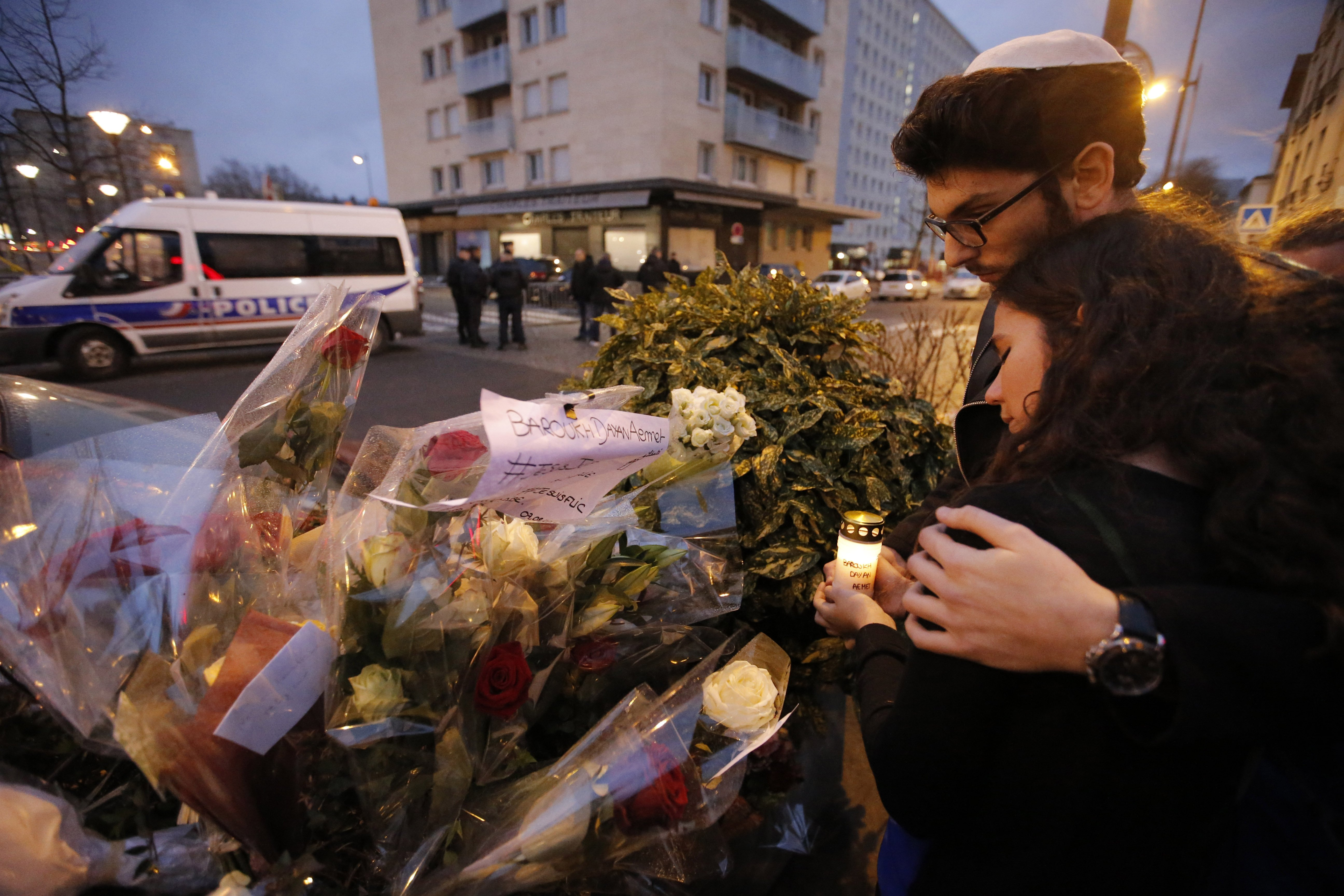 Esther Bekerman, 19, left, a cousin of one of the hostages, and Eliahou Rouas Cohen, 19, right, light a candle at a makeshift memorial near a kosher grocery store where four hostages were killed in Paris, Jan. 10, 2015.
