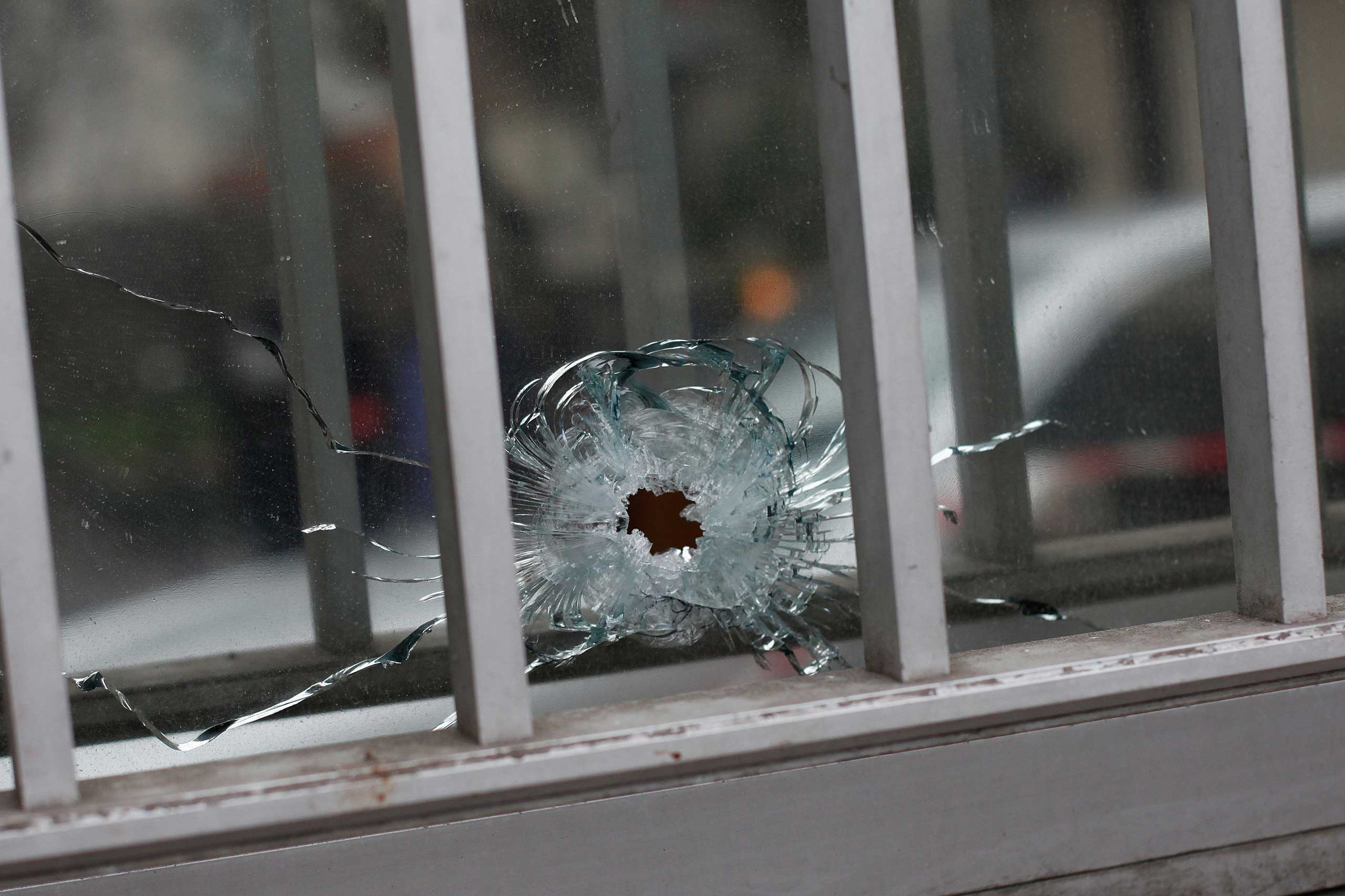 A bullet impact is seen in a window of a building next to the French satirical newspaper Charlie Hebdo's office, in Paris, Jan. 7, 2015.