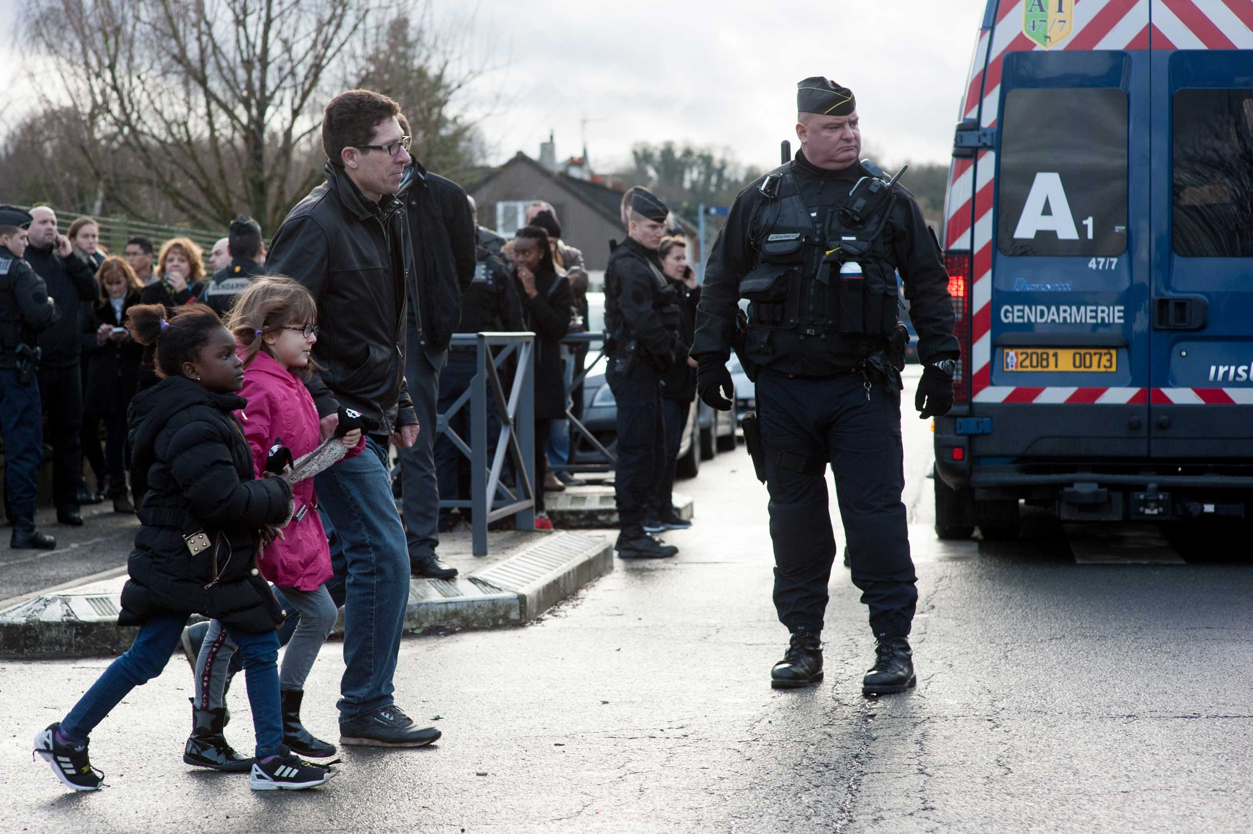 Police forces evacuate the children of the Henry-Dunant primary school located next to printing company Creation Tendance Decouverte CTD, where the two Charlie Hebdo gunmen are detaining a hostage, in Dammartin-en-Goele, north of Paris, France on Jan. 9, 2015.
