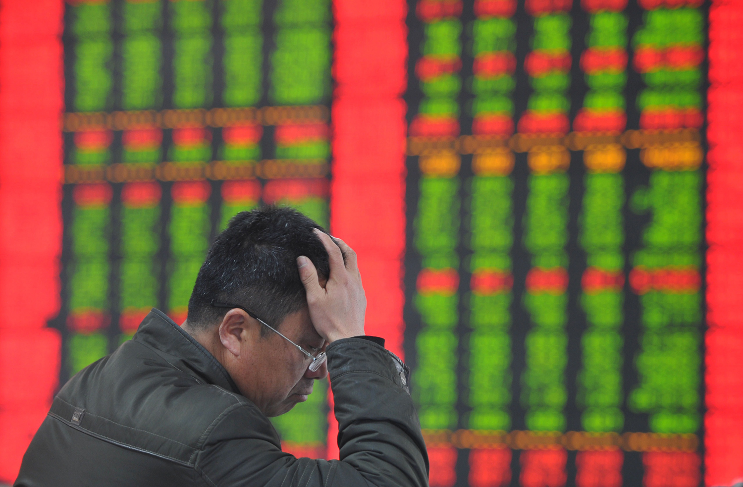 A stock investor gestures as he checks share prices at a securities firm in Fuyang, China, on Jan. 19, 2015