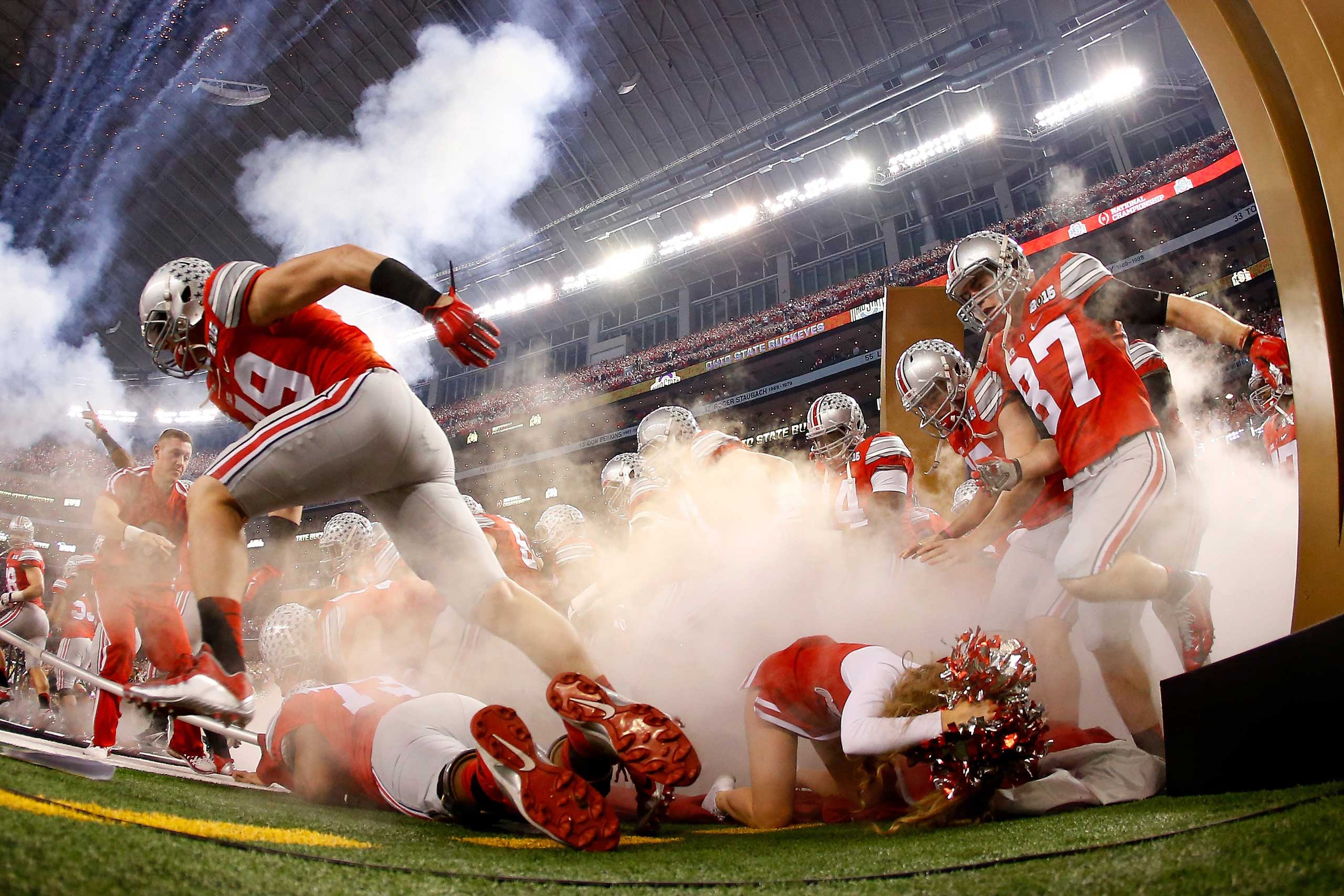 An Ohio State Buckeyes cheerleader falls as the Buckeyes run out to the field before the College Football Playoff National Championship Game on Jan. 12, 2015 in Arlington, Texas.