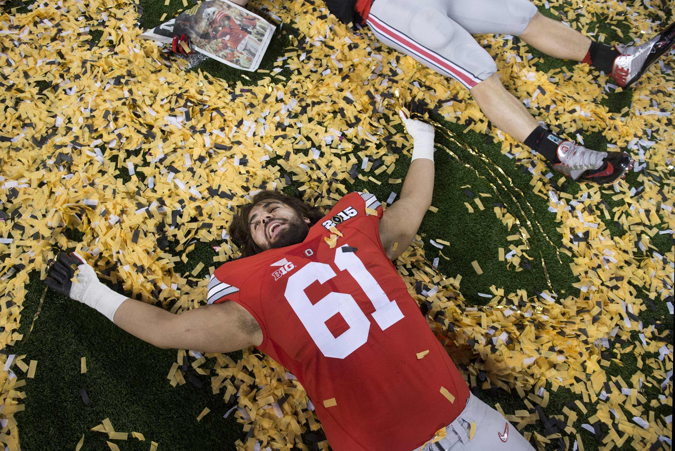 Ohio State Buckeyes offensive lineman Logan Gaskey (61) makes a snow angel in confetti as he celebrates after the Buckeyes defeated the Oregon Ducks to win the College Football Playoff National Championship, in Arlington, Texas on Jan. 12, 2015.