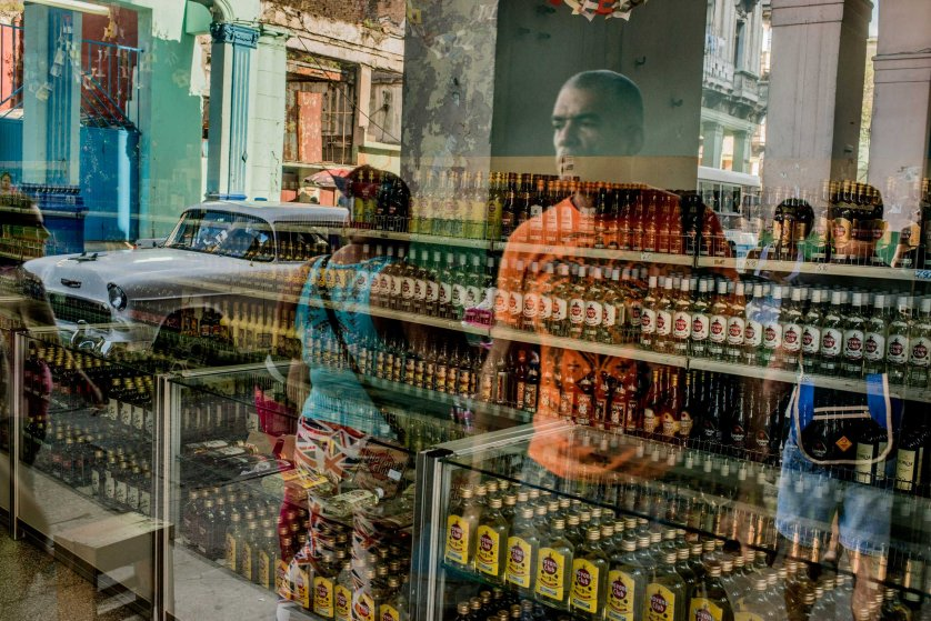 People outside a shop selling rum are reflected in the windows, in Havana, Dec. 22, 2014.