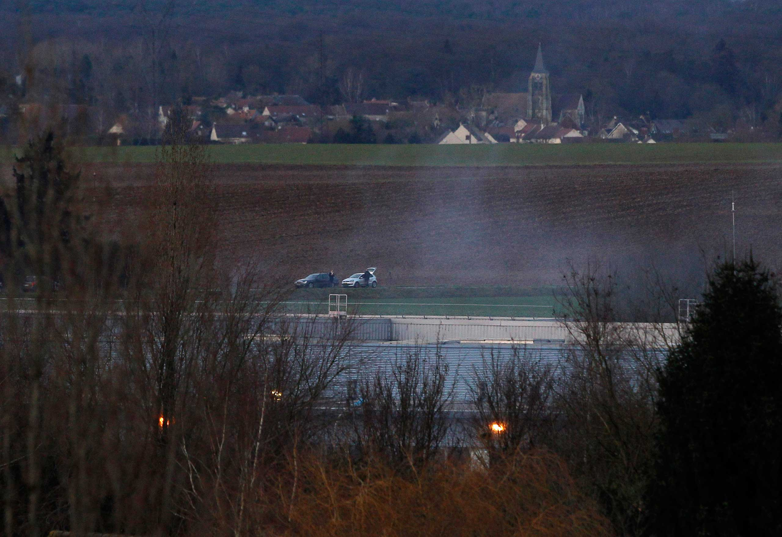 Smoke rises from a building in Dammartin-en-Goele, northeast of Paris, where the two brothers suspected in a deadly terror attack were cornered,  Jan. 9, 2015.