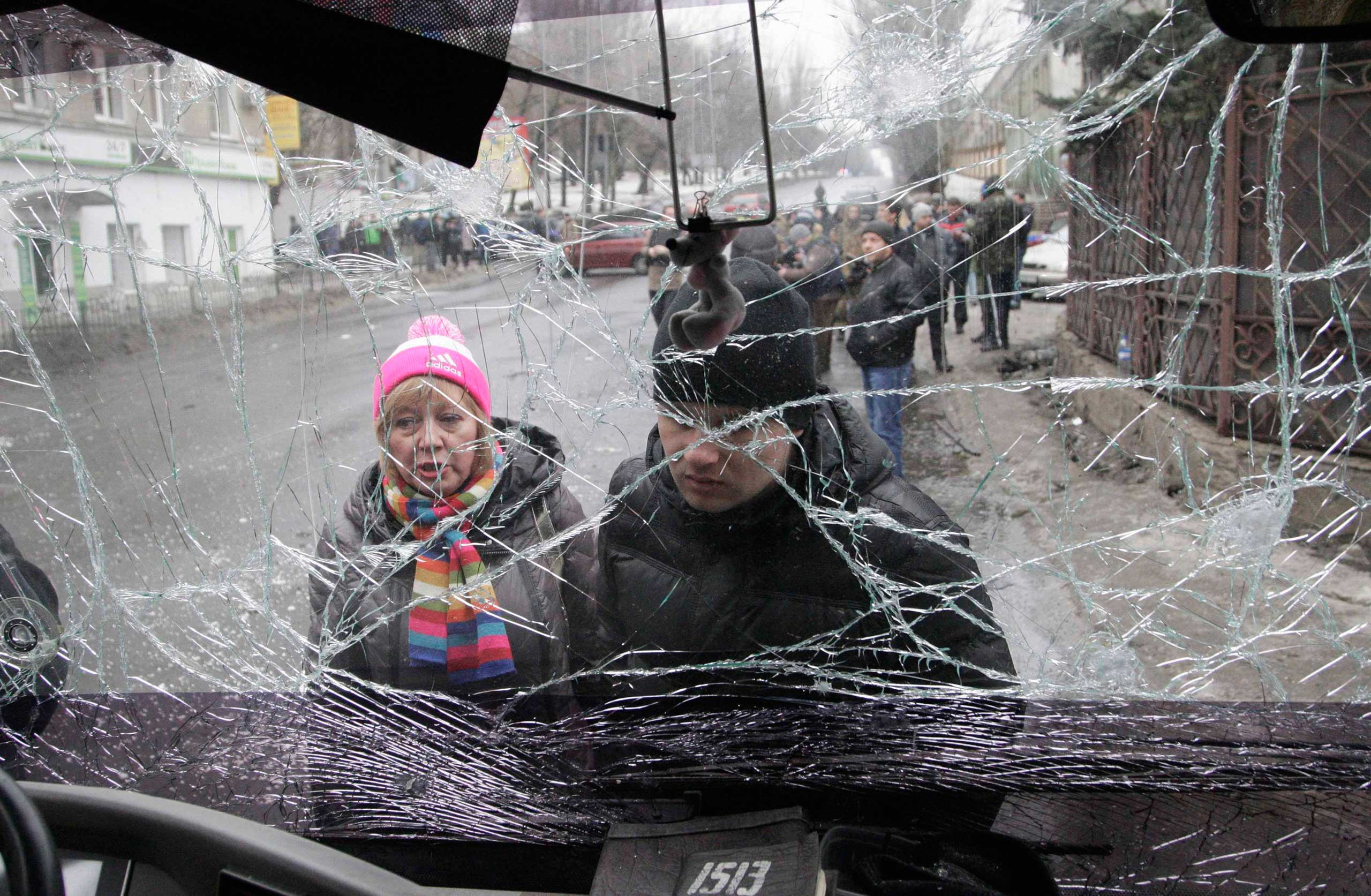 People look through the front windshield of a damaged trolleybus in Donetsk, Jan. 22, 2015.