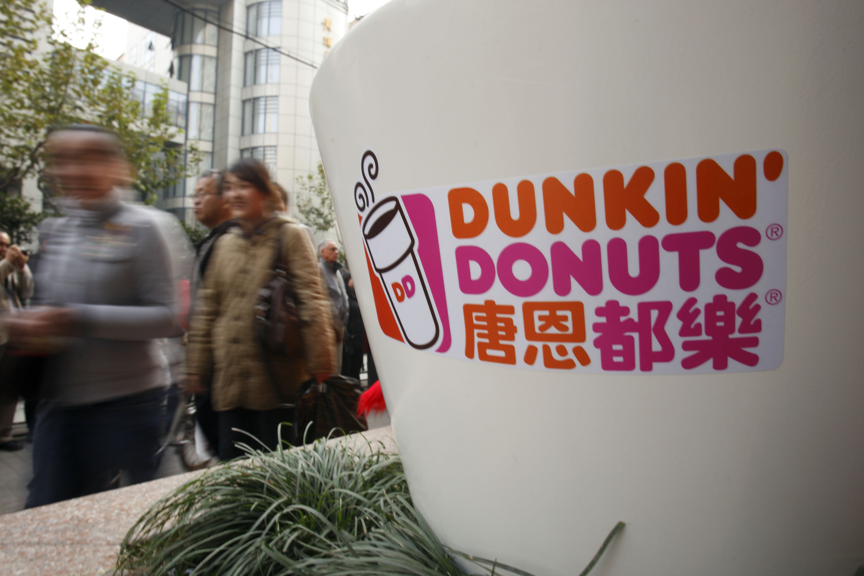 Pedestrians walk past the Dunkin' Donuts logo at the opening ceremony of the company's flagship store in Shanghai, China, on Nov. 20, 2008.