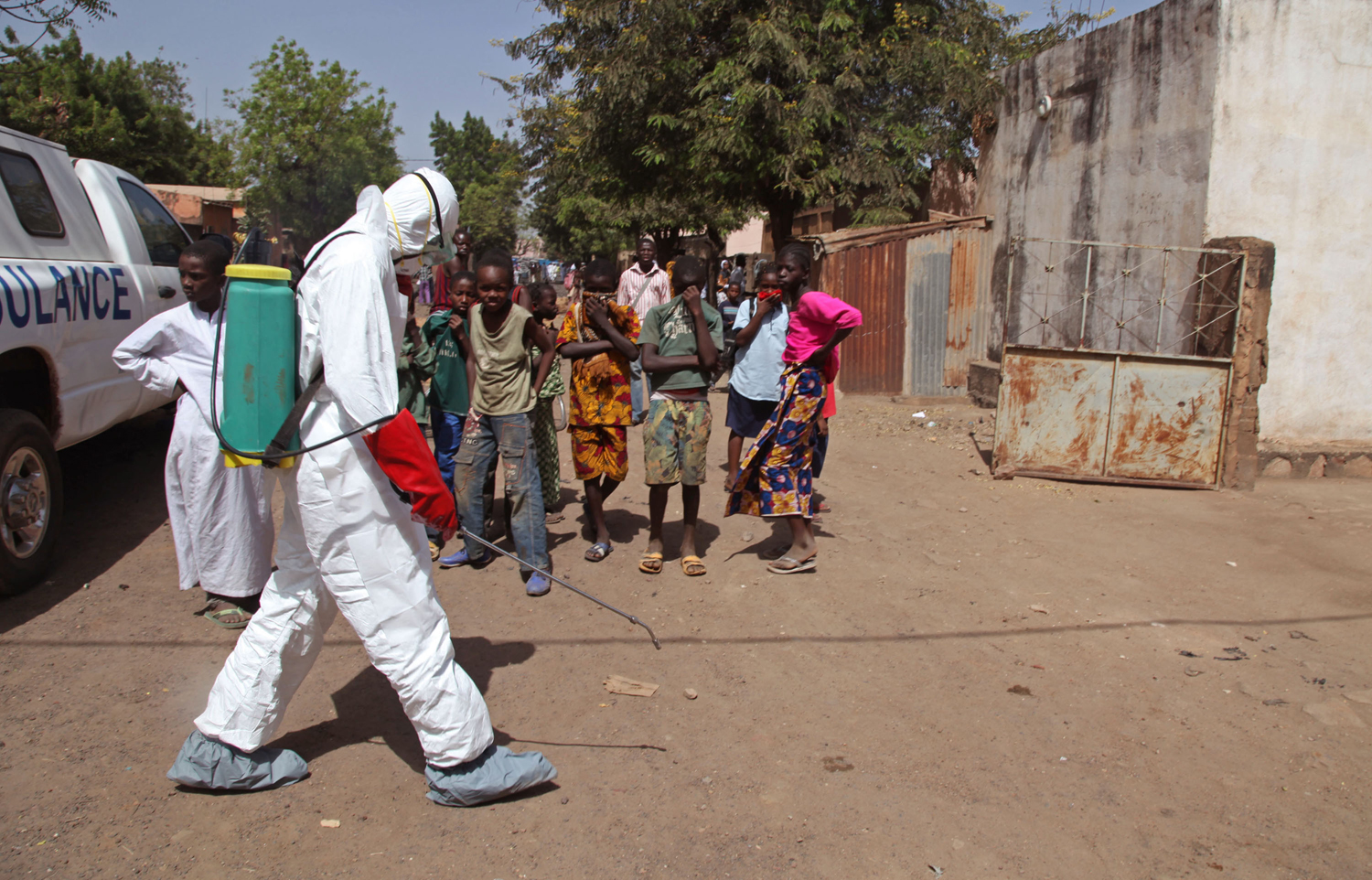A health worker sprays disinfectants near a mosque, after the body of a man suspected of dying from the Ebola virus was washed inside before being buried  in Bamako, Mali