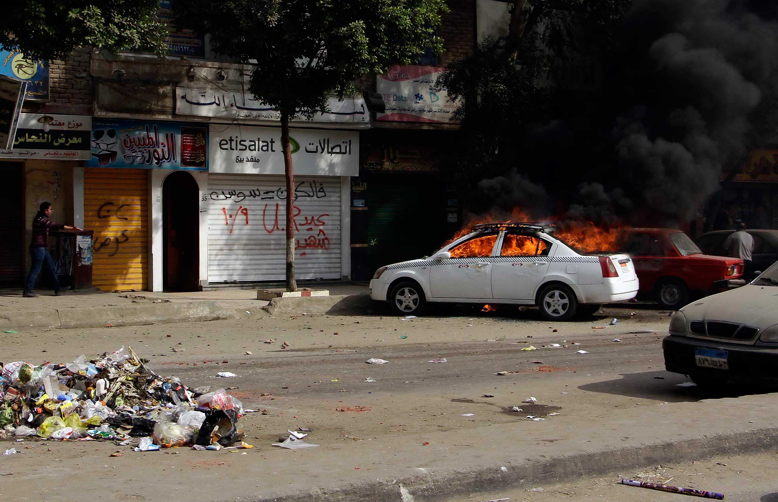 A taxi burns during clashes with  Egyptian security forces in the district of Matariyah, eastern Cairo, Jan. 25, 2015.