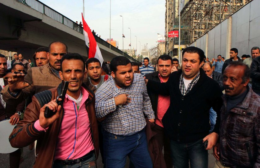 Man holds his chest as he is arrested by plainclothes police in downtown Cairo, Jan. 25, 2015.
