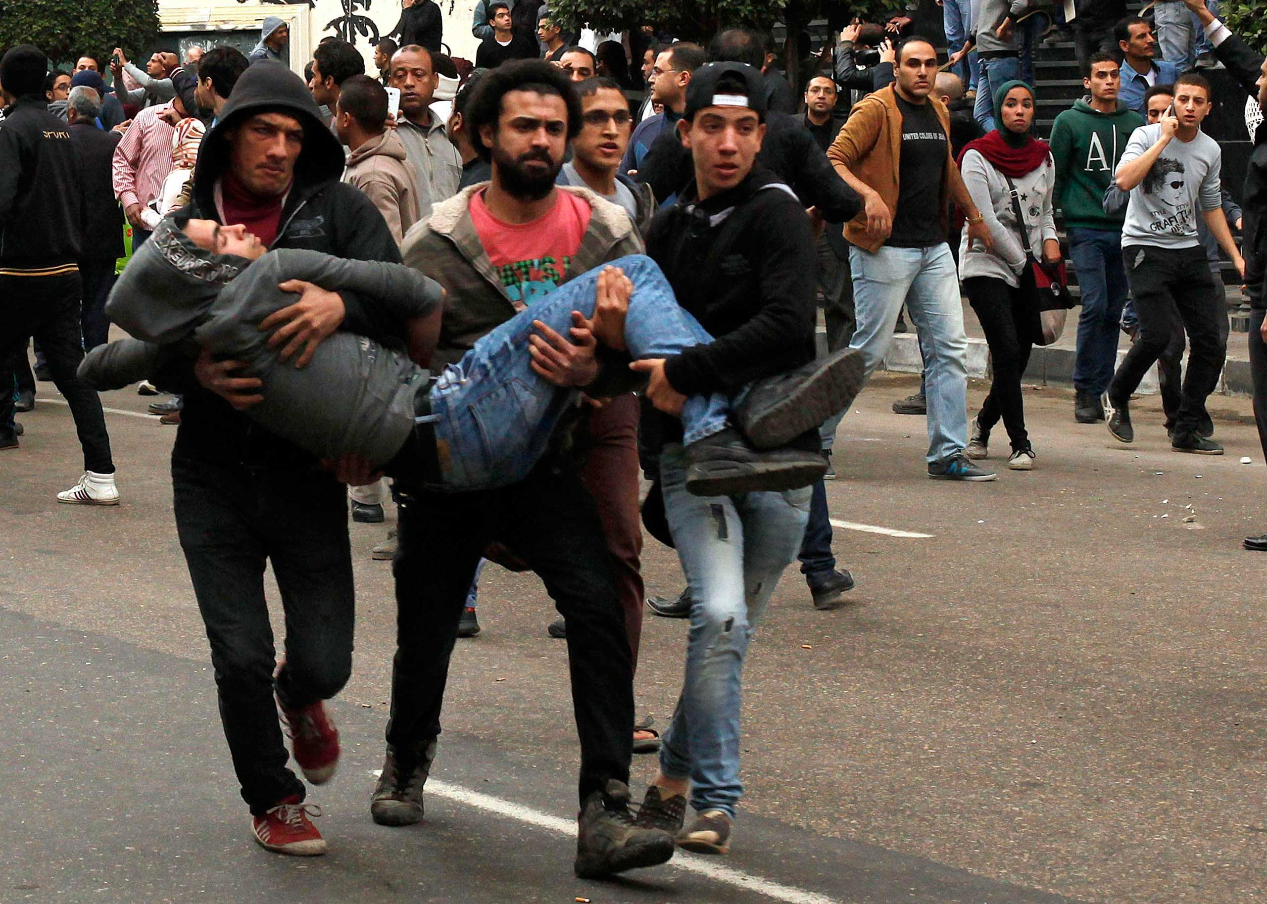 Anti-government protesters help an injured protester when pro-government protesters threw stones during a protest in front of the press syndicate in Cairo, Jan. 25, 2015.