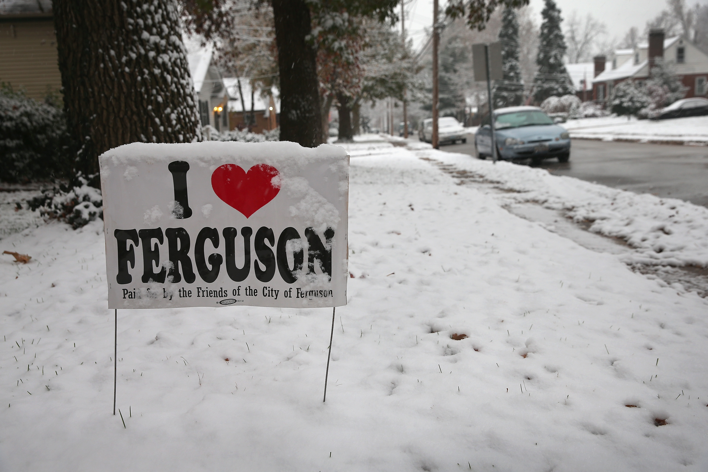 Snow covers a yard sign placed outside a home near the police station on Nov. 16, 2014 in Ferguson, Missouri.