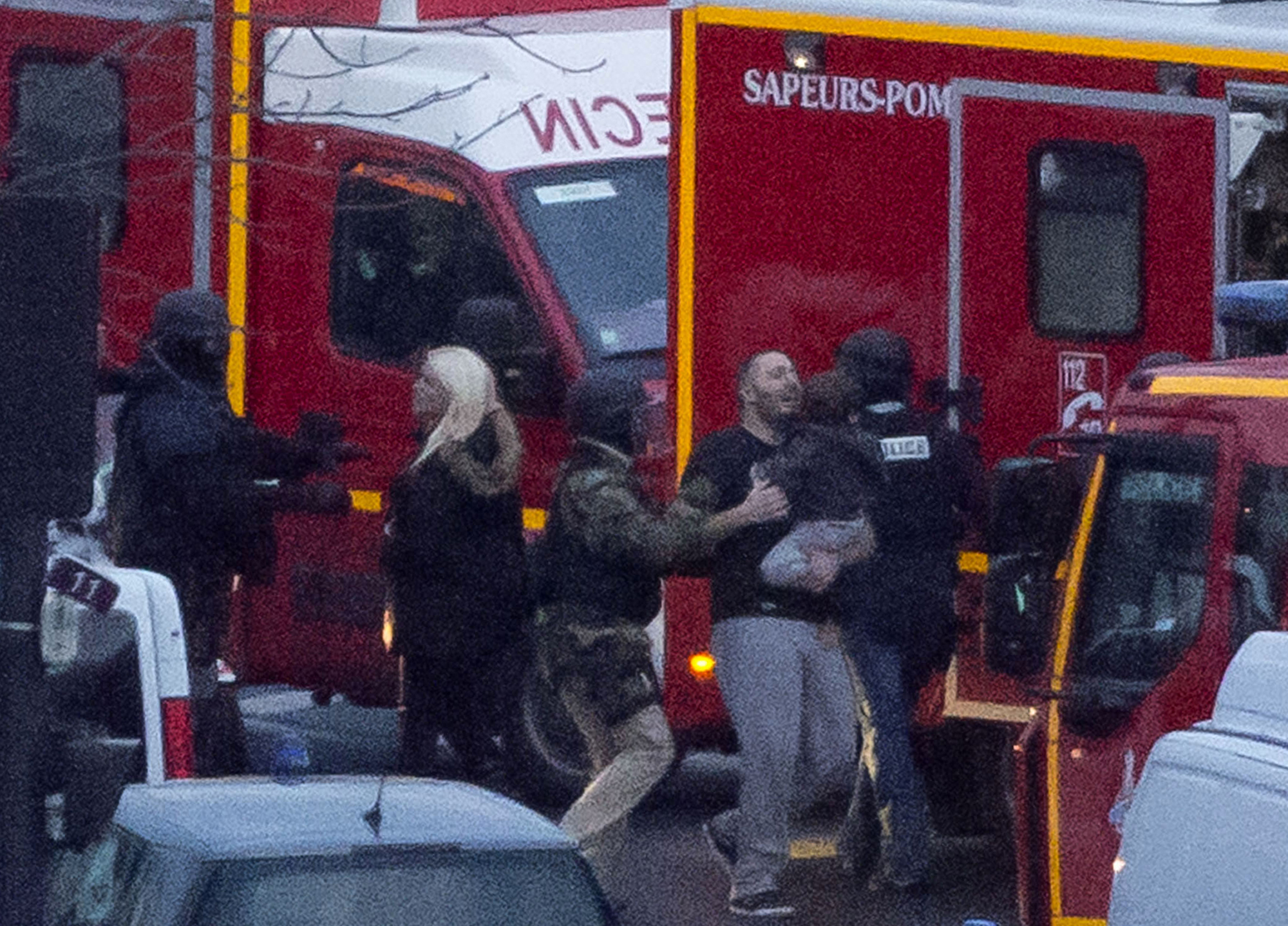 This is a Friday, Jan. 9, 2015 file photo of a security officer directs released hostages after they stormed a kosher market to end a hostage situation, Paris. Explosions and gunshots were heard as police forces stormed a kosher grocery in Paris where a gunman was holding at least five people hostage. At the kosher supermarket in Paris, a quick-thinking Muslim employee hides several Jewish shoppers in the basement before sneaking out to brief police on the hostage-taker upstairs. (AP Photo/Michel Euler, File)