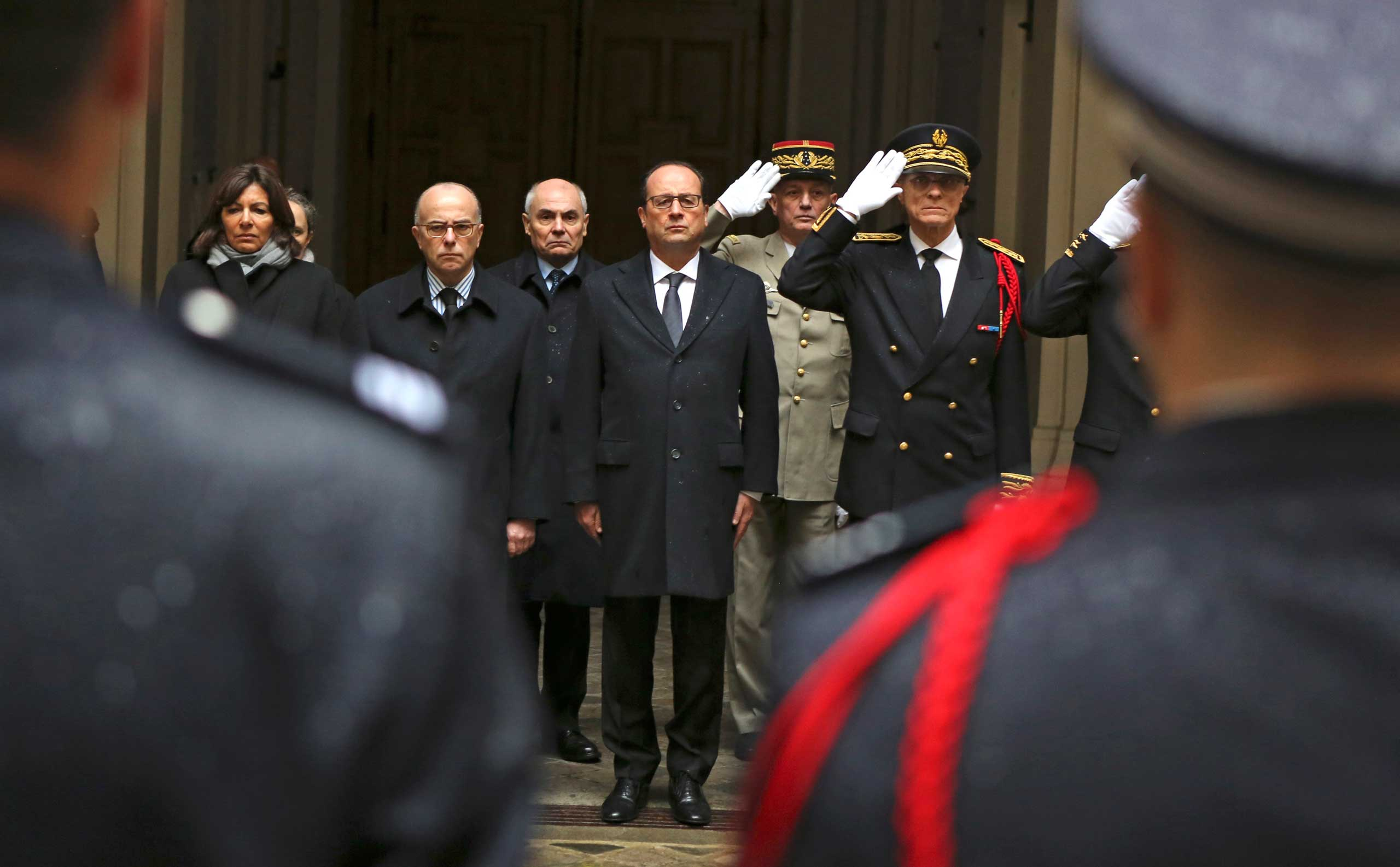 French President Francois Hollande, center, with interior minister Bernard Cazeneuve, left, and Paris police prefect Bernard Boucault, right, stands for a minute of silence, at Paris Prefecture in Paris, Jan. 8, 2015.