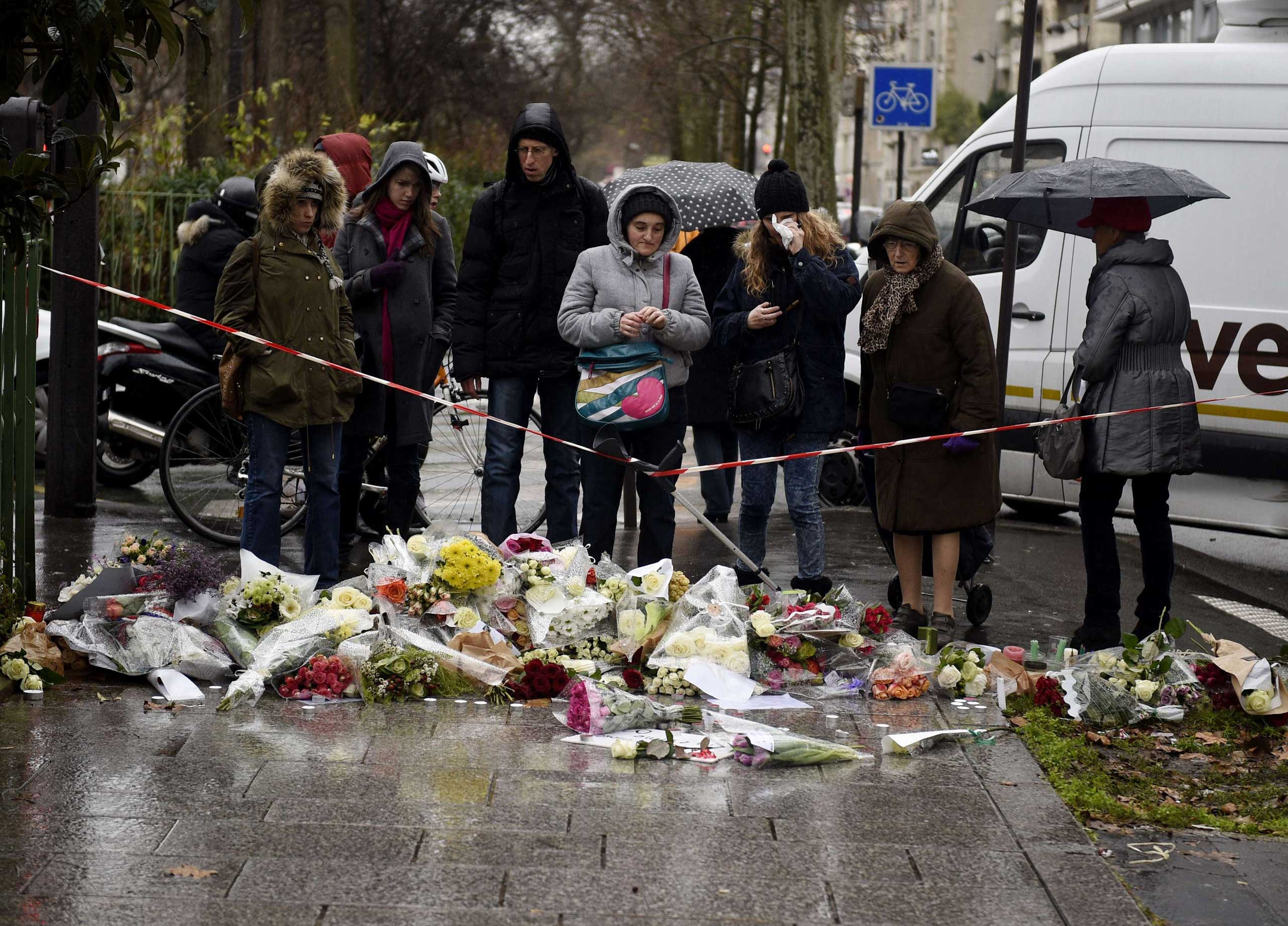 Floral tributes are laid on the ground during a minutes silence in Paris on Jan. 8, 2015.