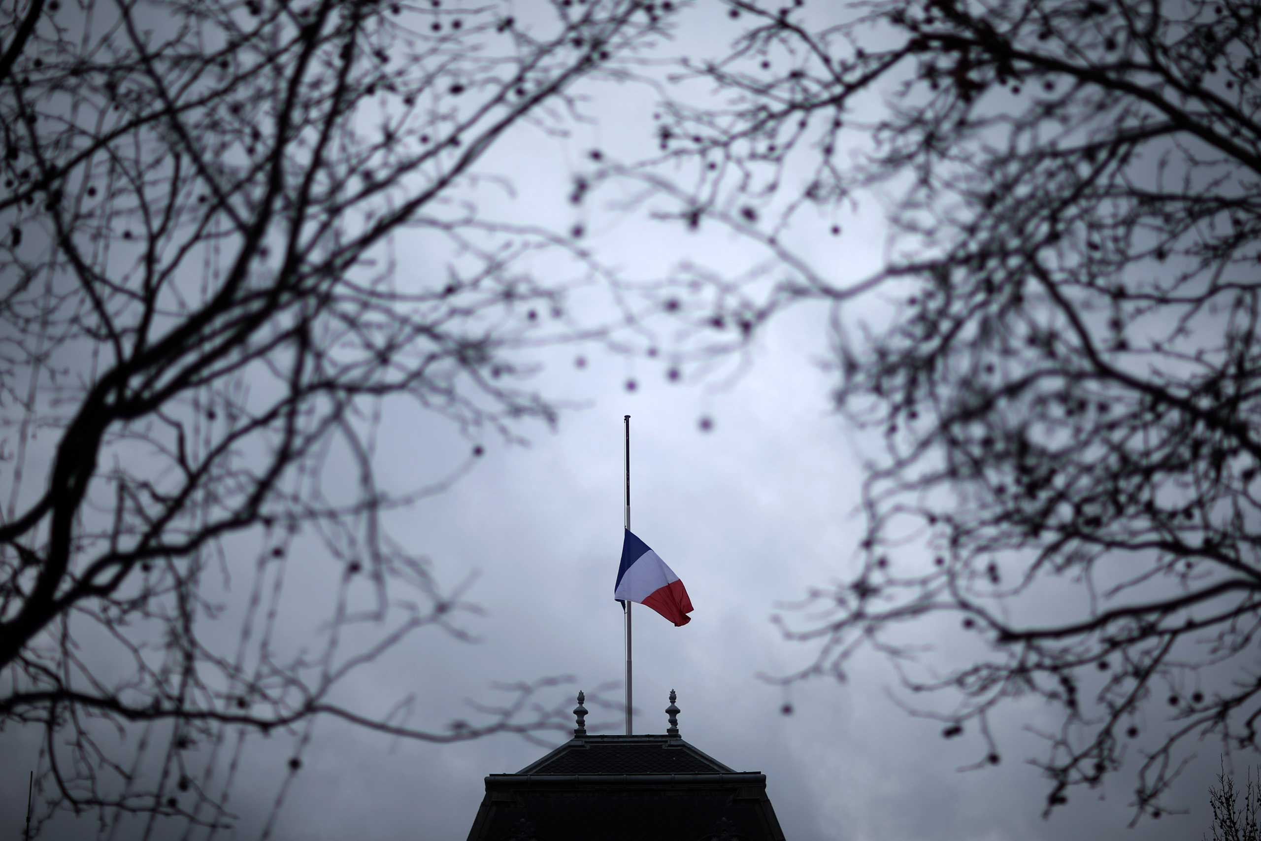 The French national flag waves at a half mast on a building in Paris, Jan. 8,2015.