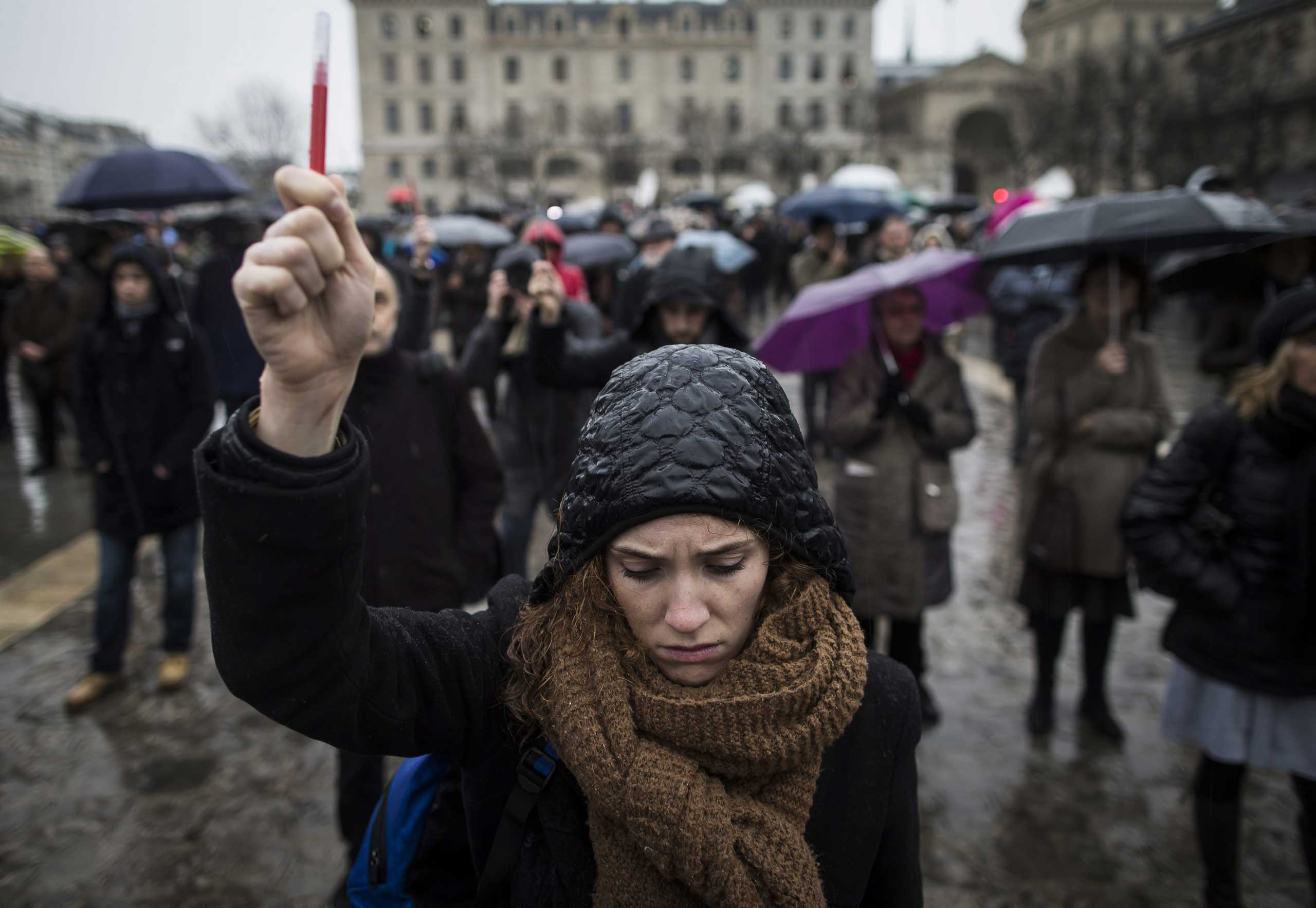 A young woman holds aloft a symbolic pen as she joins others gathered for a minute of silence in front of Notre Dame cathedral, in Paris, Jan. 8, 2014.